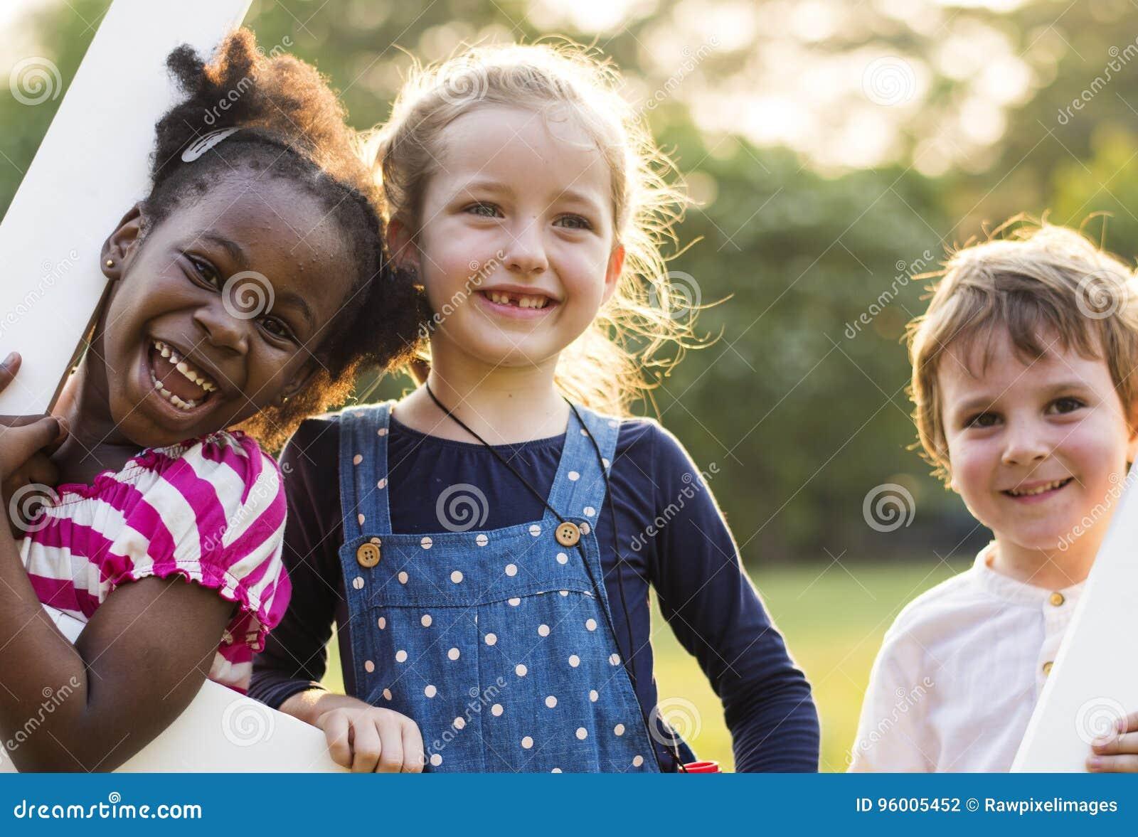 O grupo de jardim de infância caçoa os amigos que jogam o divertimento do campo de jogos e a manutenção programada
