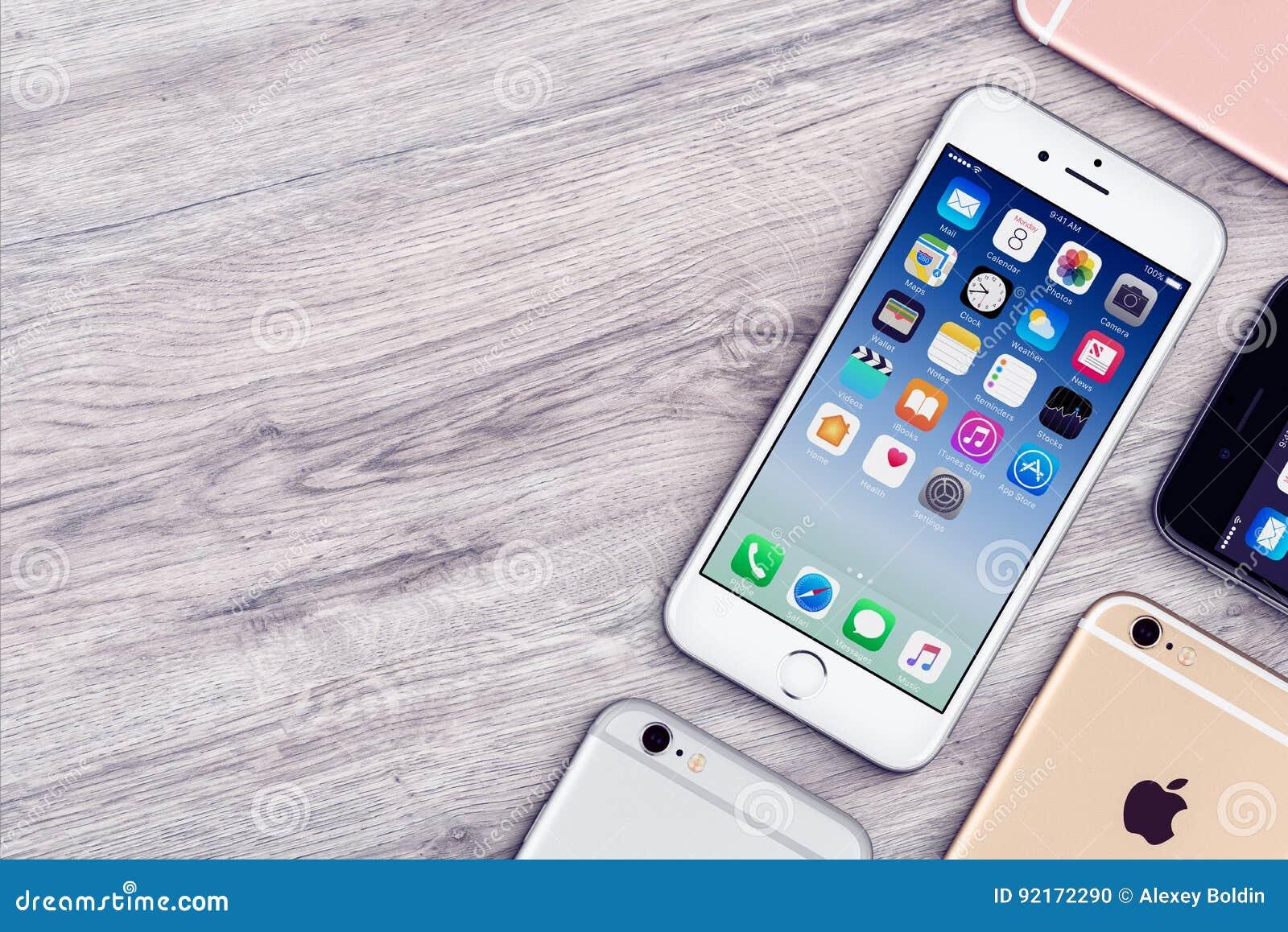 O grupo de opinião superior colocada dos iPhones 6s de Apple plano colorido encontra-se na mesa de escritório de madeira com espa
