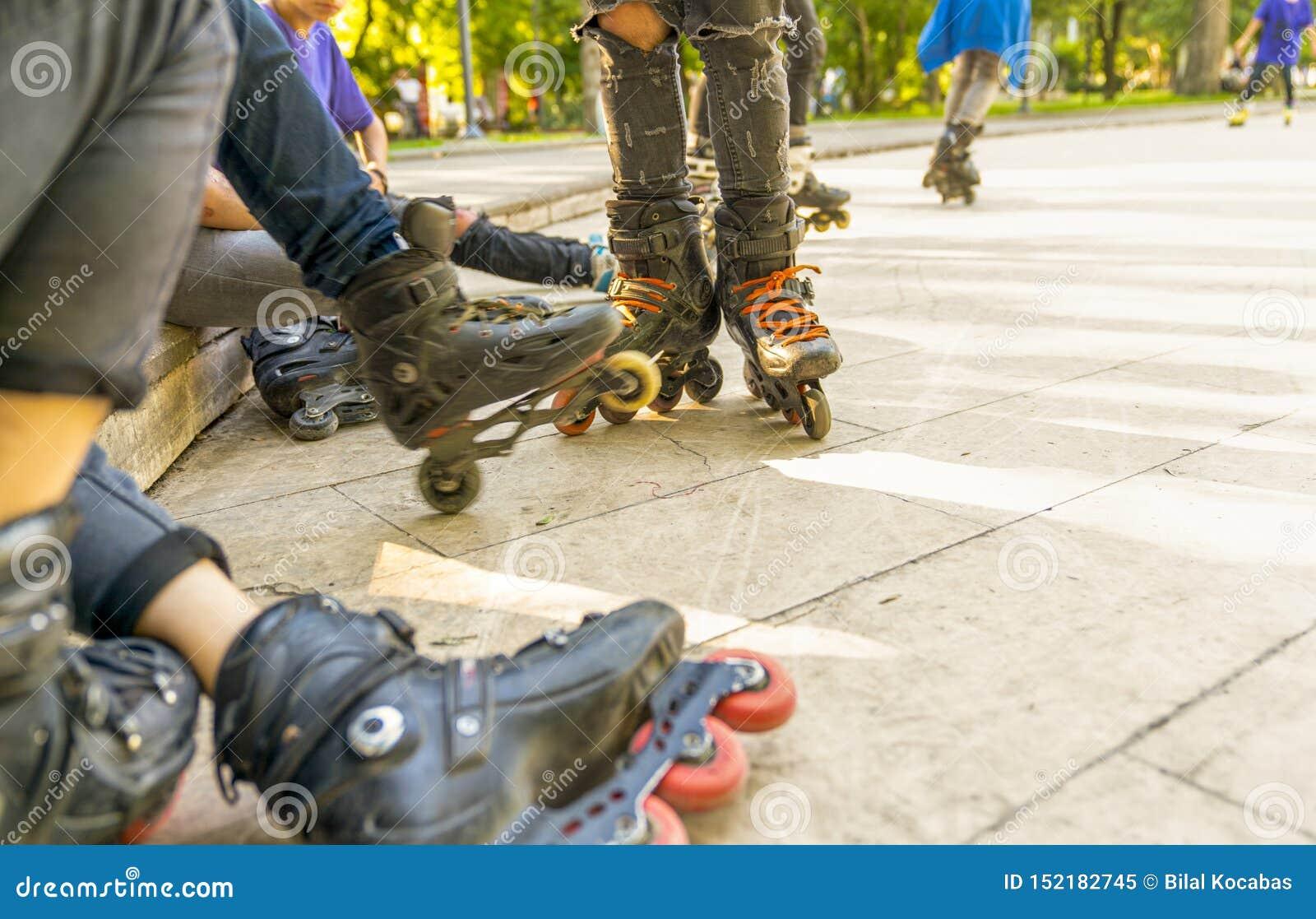 O grupo de patins de rolo que sentam-se e que descansam no parque exterior do patim, fecha-se acima da vista das rodas antes de p