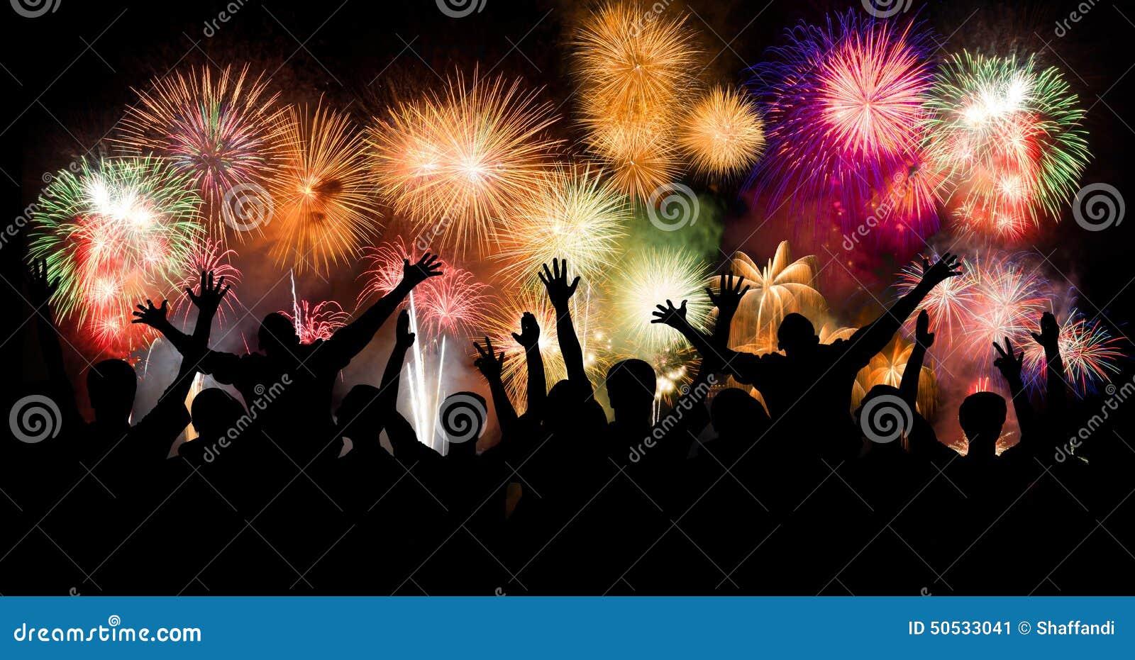 O grupo de pessoas que aprecia fogos-de-artifício espetaculares mostra em um carnaval ou em um feriado