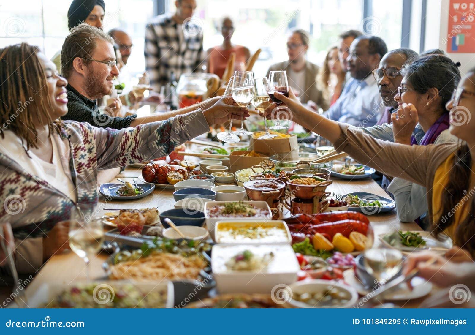 O grupo de povos diversos está tendo o almoço junto