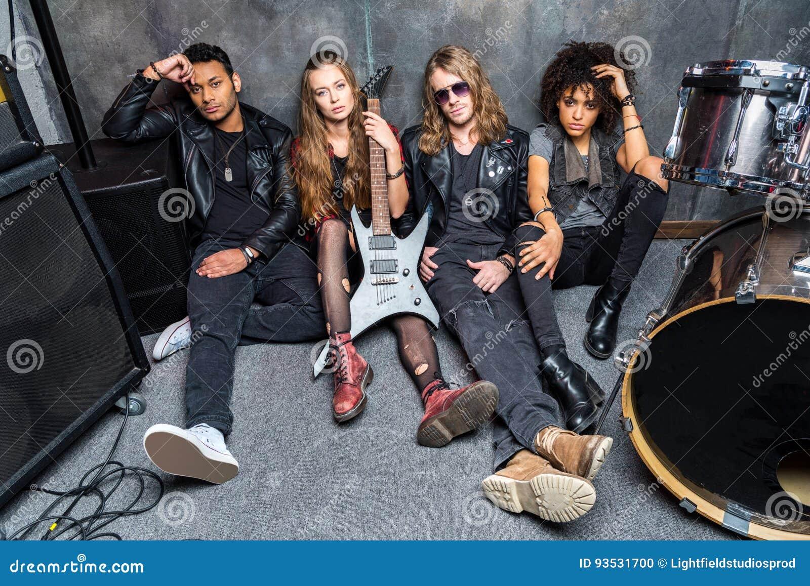 O grupo de rock que senta-se no assoalho ao descansar após ensaia
