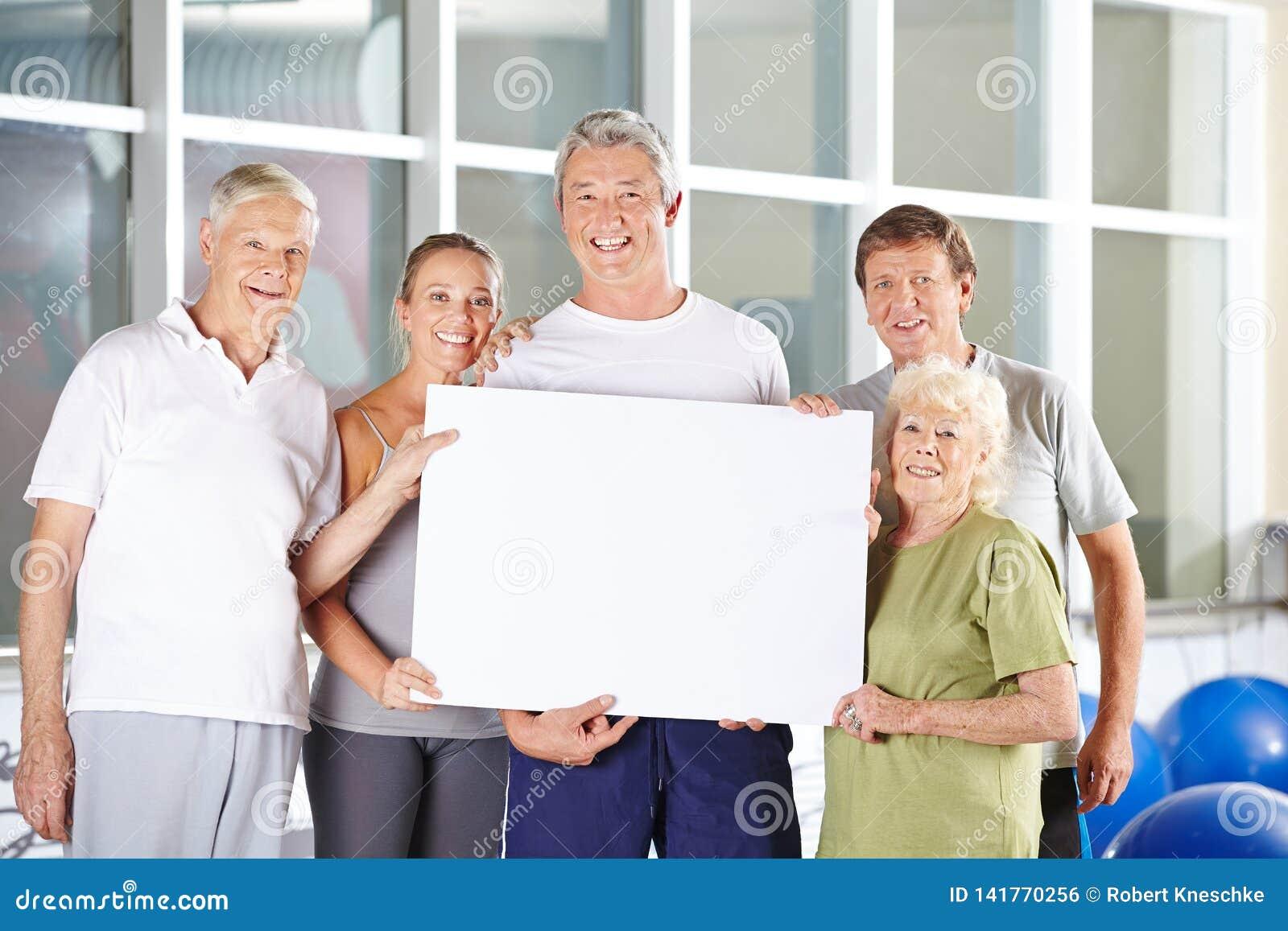O grupo de sêniores guarda o quadro de avisos vazio no fitness center