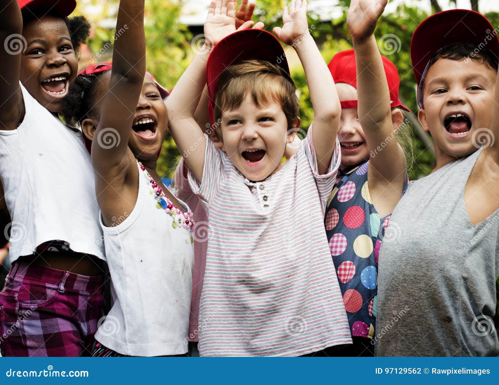 O grupo de sorriso levantado mão da felicidade dos amigos da escola das crianças aprende
