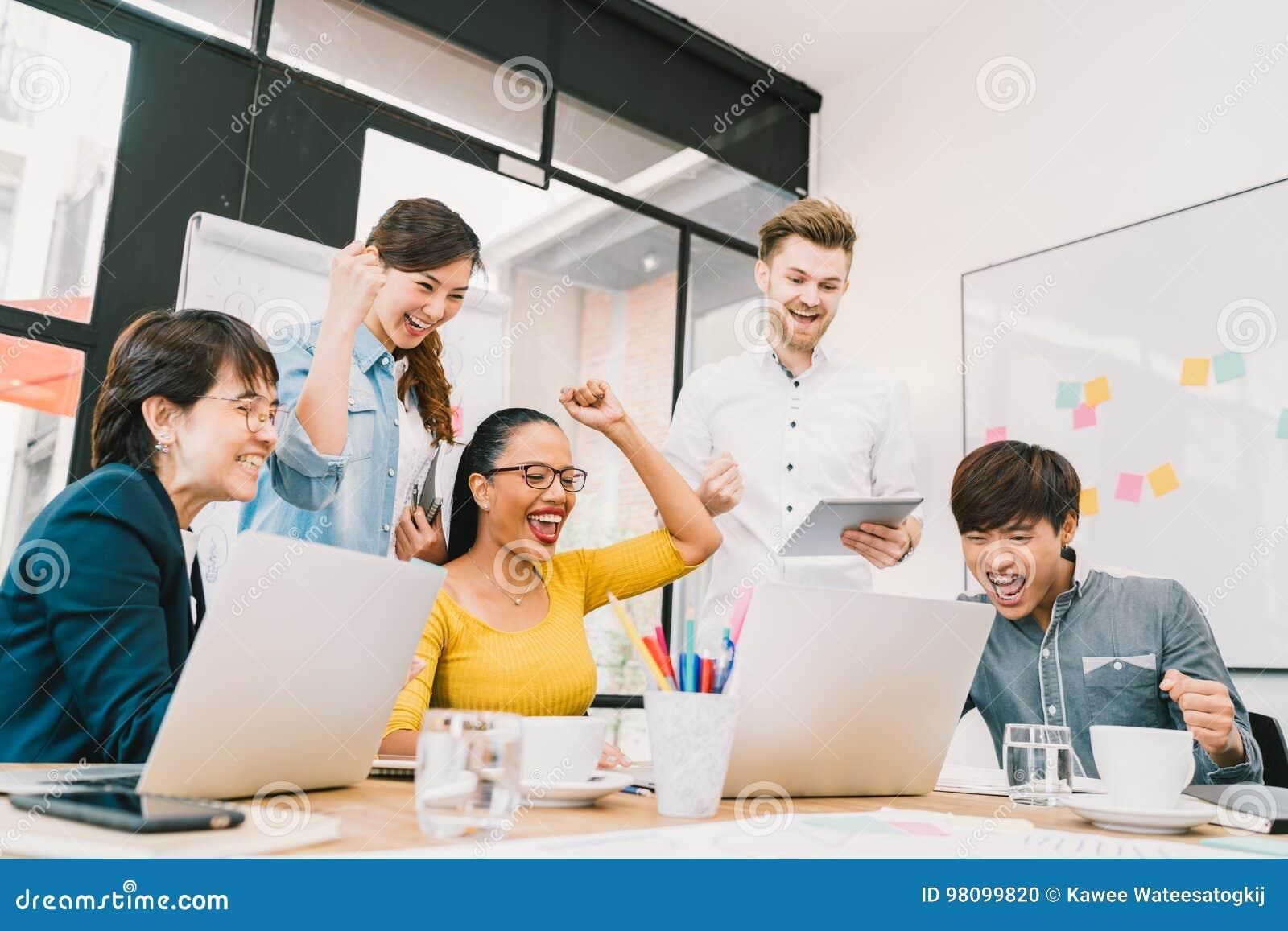 O grupo diverso multi-étnico de colegas de trabalho comemora junto com o portátil e a tabuleta Equipe criativa ou colega ocasiona