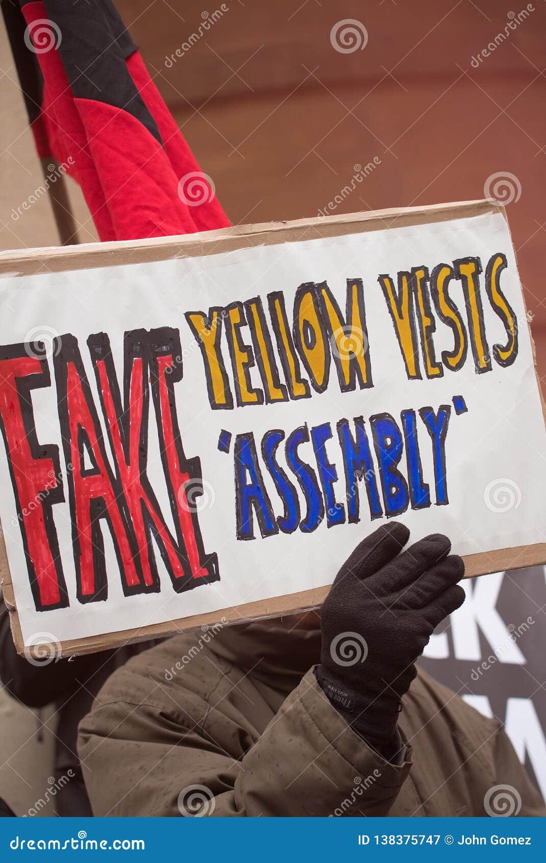 O grupo pequeno de anti anarquistas irritados do governo encena um protesto no lugar de Portland, Londres
