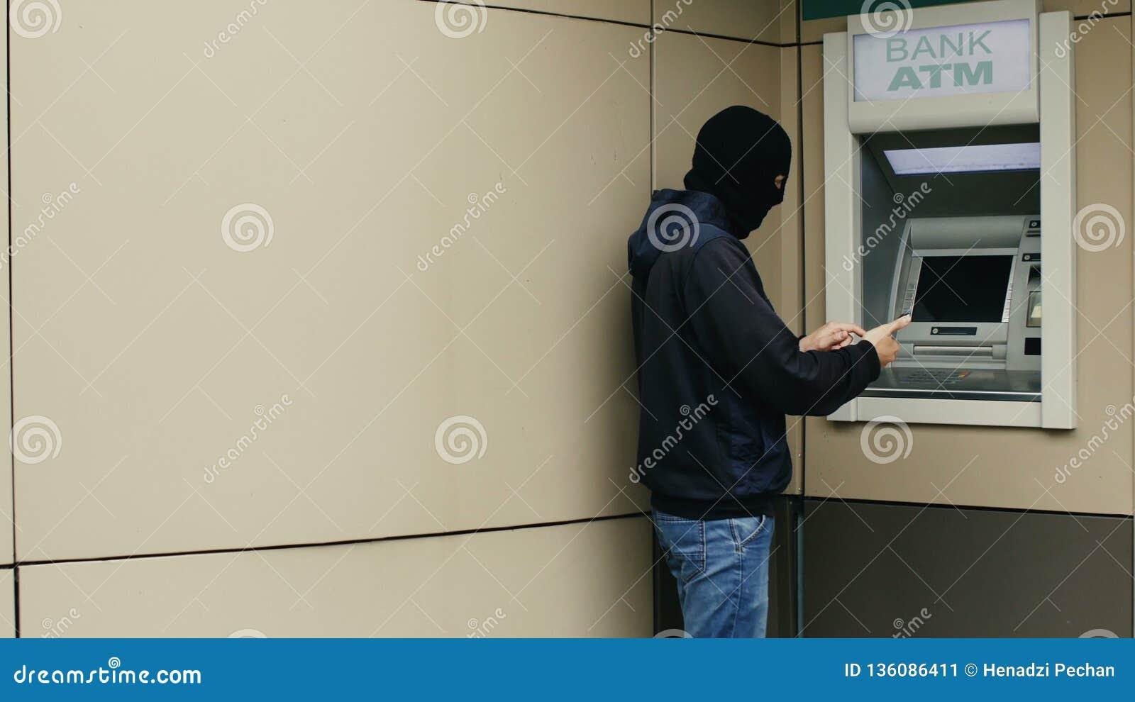 O hacker ou o ladrão com smartphone roubam a informação ou os dados do banco ATM