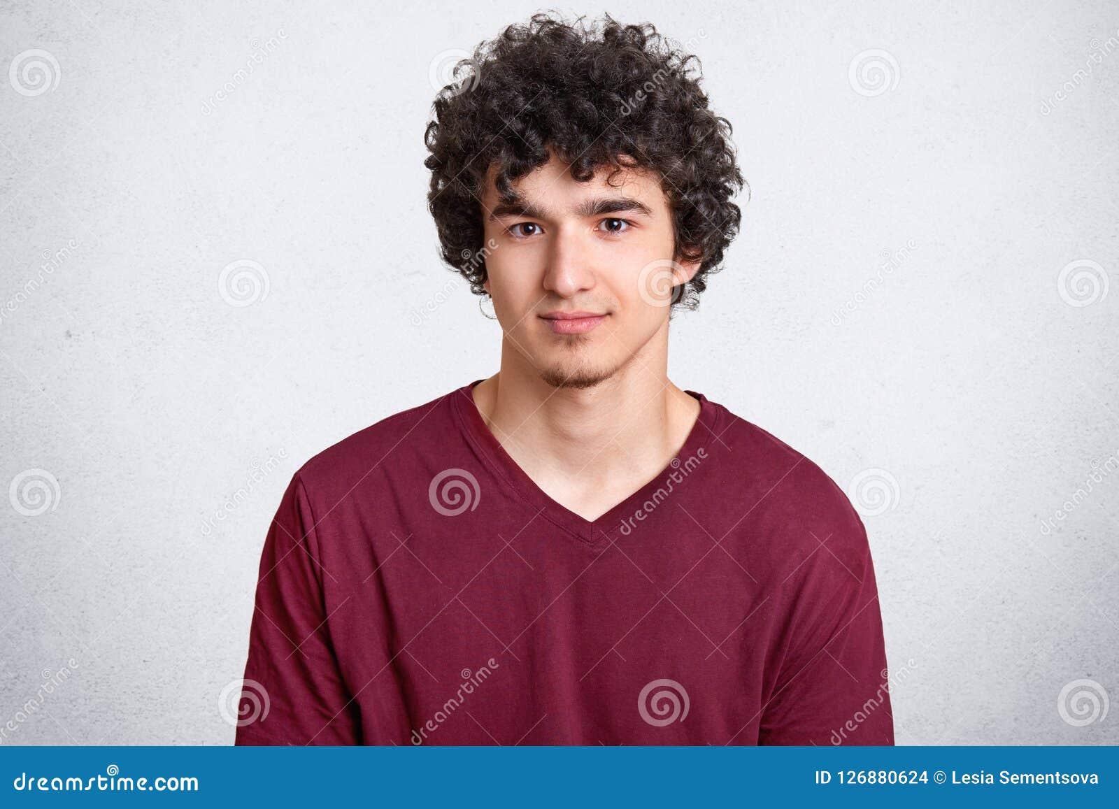 O Headshot do jovem encaracolado atrativo olha seriamente na câmera, tem olhar atraente, passa o tempo livre com os amigos, vesti