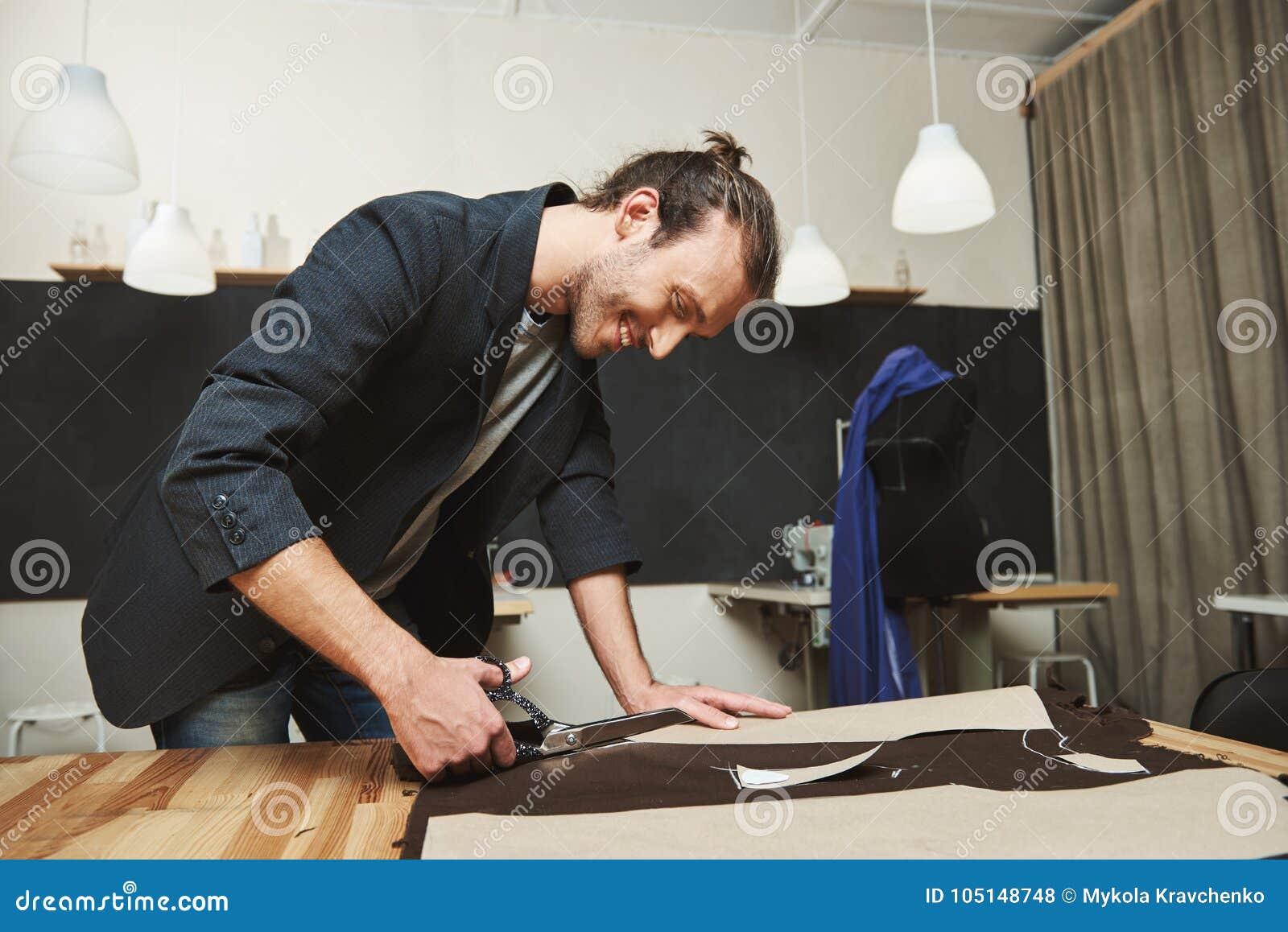 O hispânico de cabelo escuro atrativo alegre maduro, desenhador de moda masculino que trabalha no vestido novo na oficina, cortan