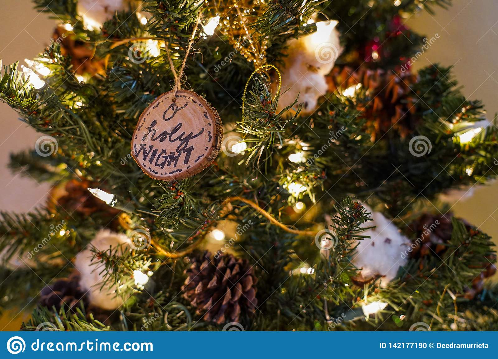 O holy night and other ornaments on a christmas tree