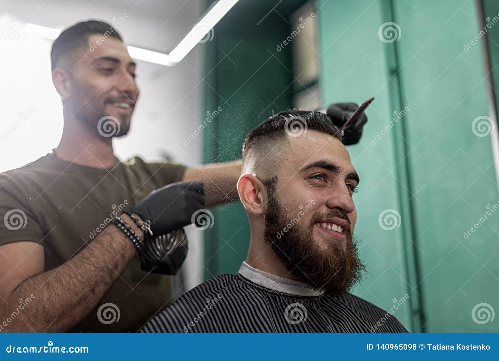 O homem à moda com uma barba senta-se e sorri-se em uma barbearia O barbeiro em luvas pretas faz a pulverização para o penteado