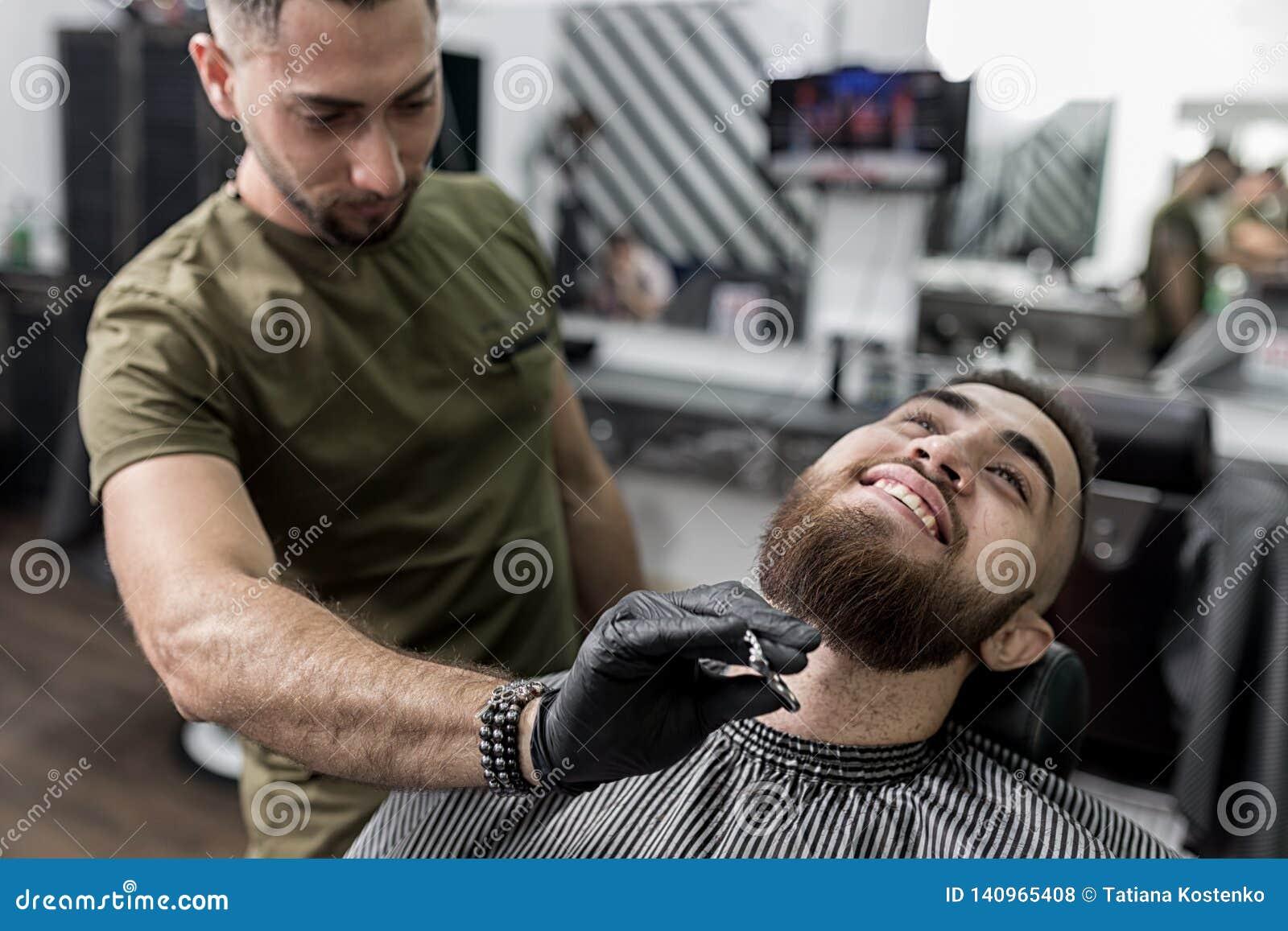 O homem à moda com uma barba senta-se em um barbeiro O barbeiro apara a barba dos homens com tesouras