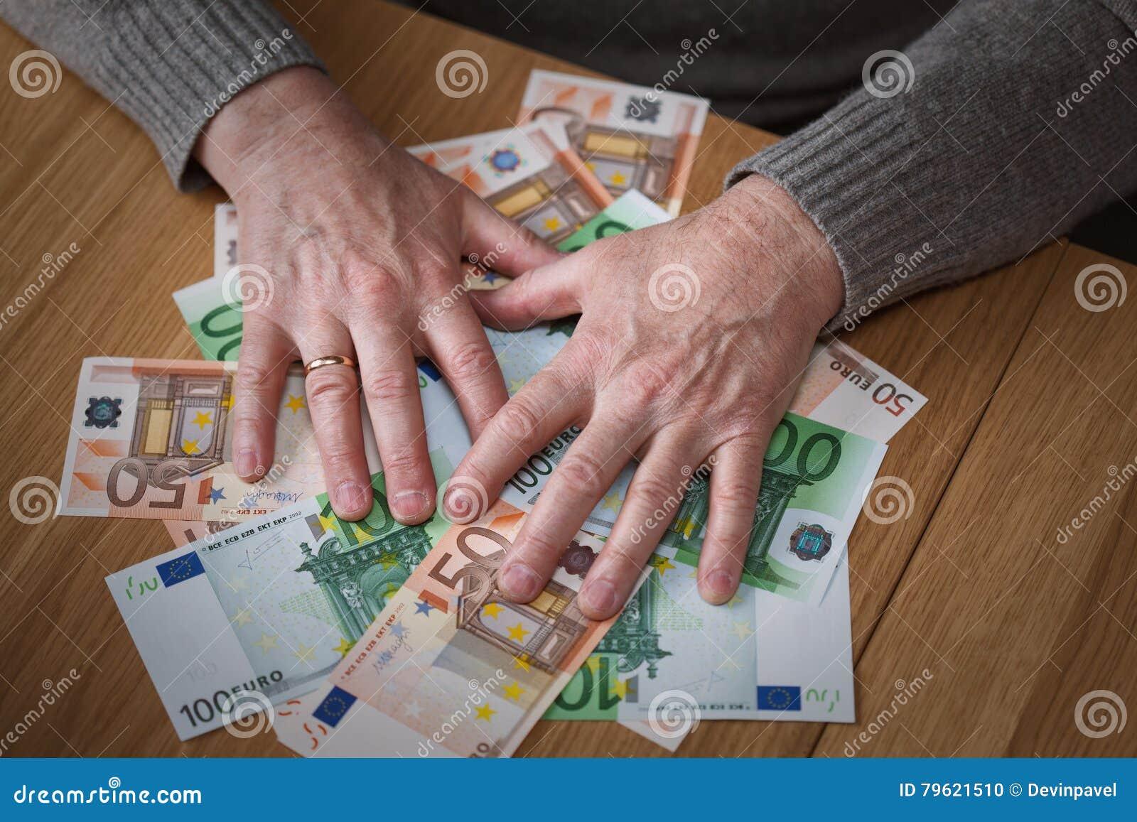 O homem ávido fecha cédulas do Euro das mãos