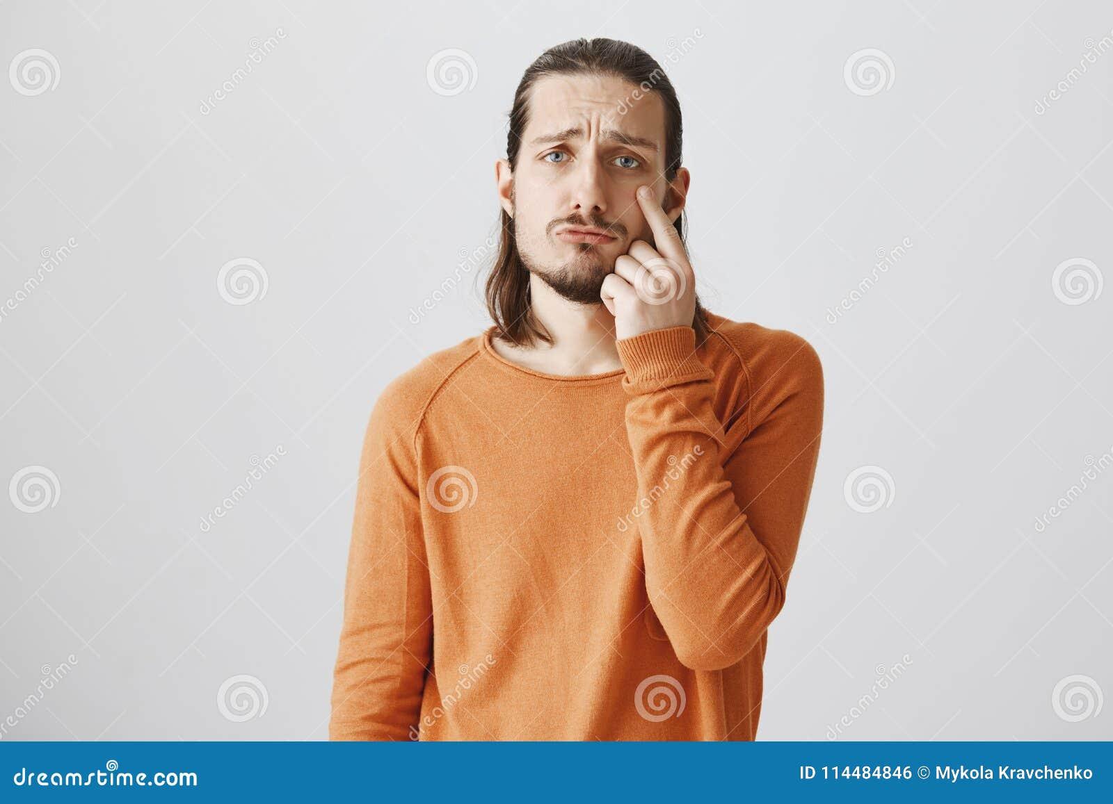 O homem é movido para rasgos Tiro interno do homem adulto atrativo com barba que aponta na pálpebra, sendo sombrio e dirigindo em