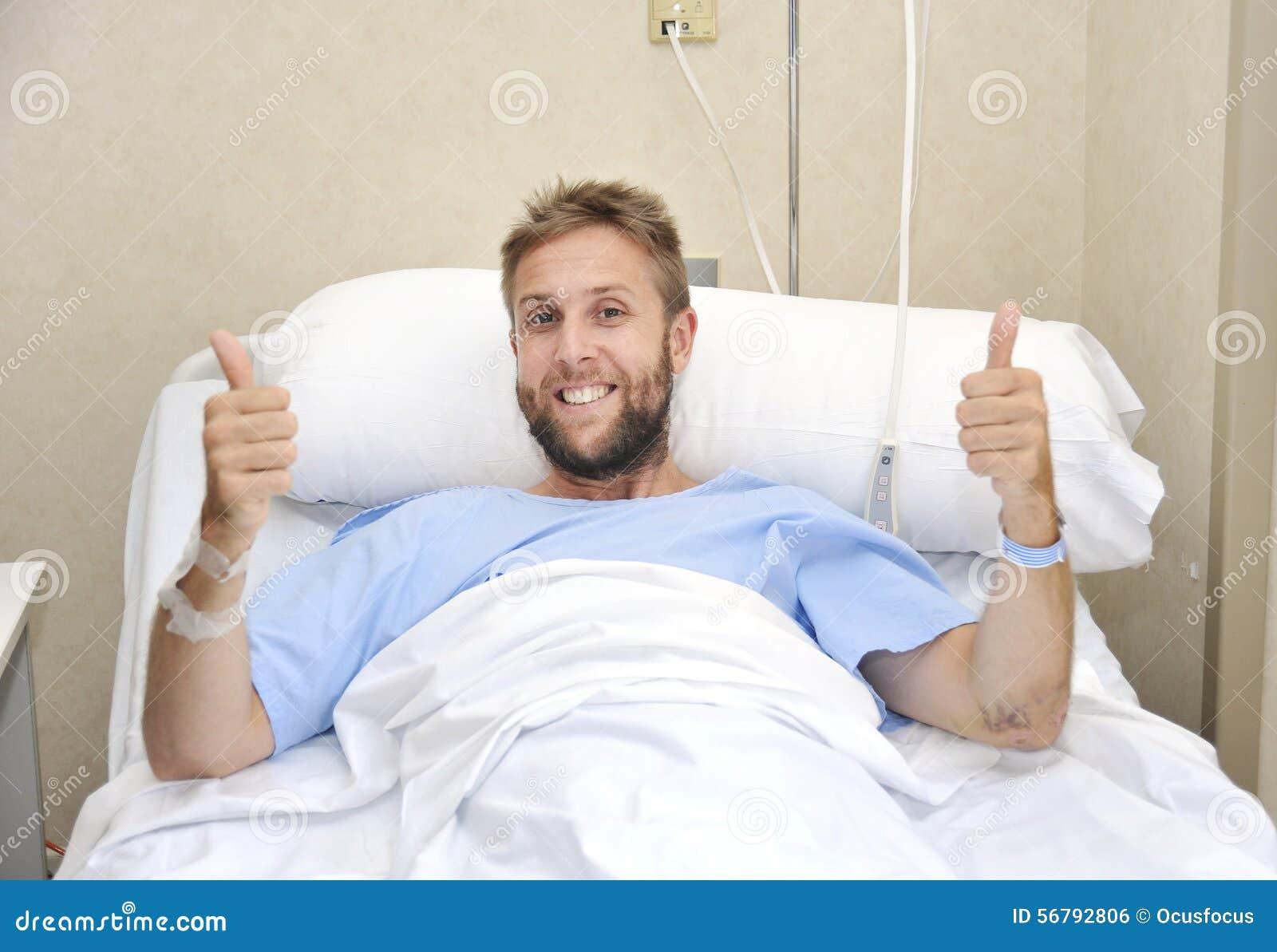 O homem americano novo que encontra-se na cama na sala de hospital doente ou doente mas que dá manuseia acima do sorriso feliz e