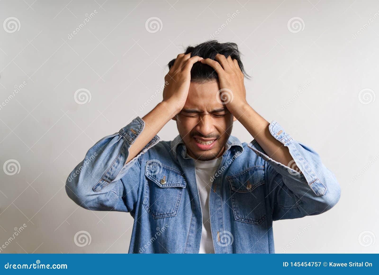 O homem asiático novo pôs as mãos a sua cabeça Ele doente de sentimento e dor de cabeça devido a ter alguns problemas Seu es