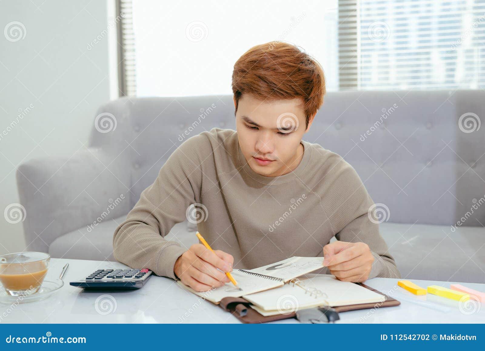 O homem asiático que faz finanças e calcula sobre o escritório do custo em casa