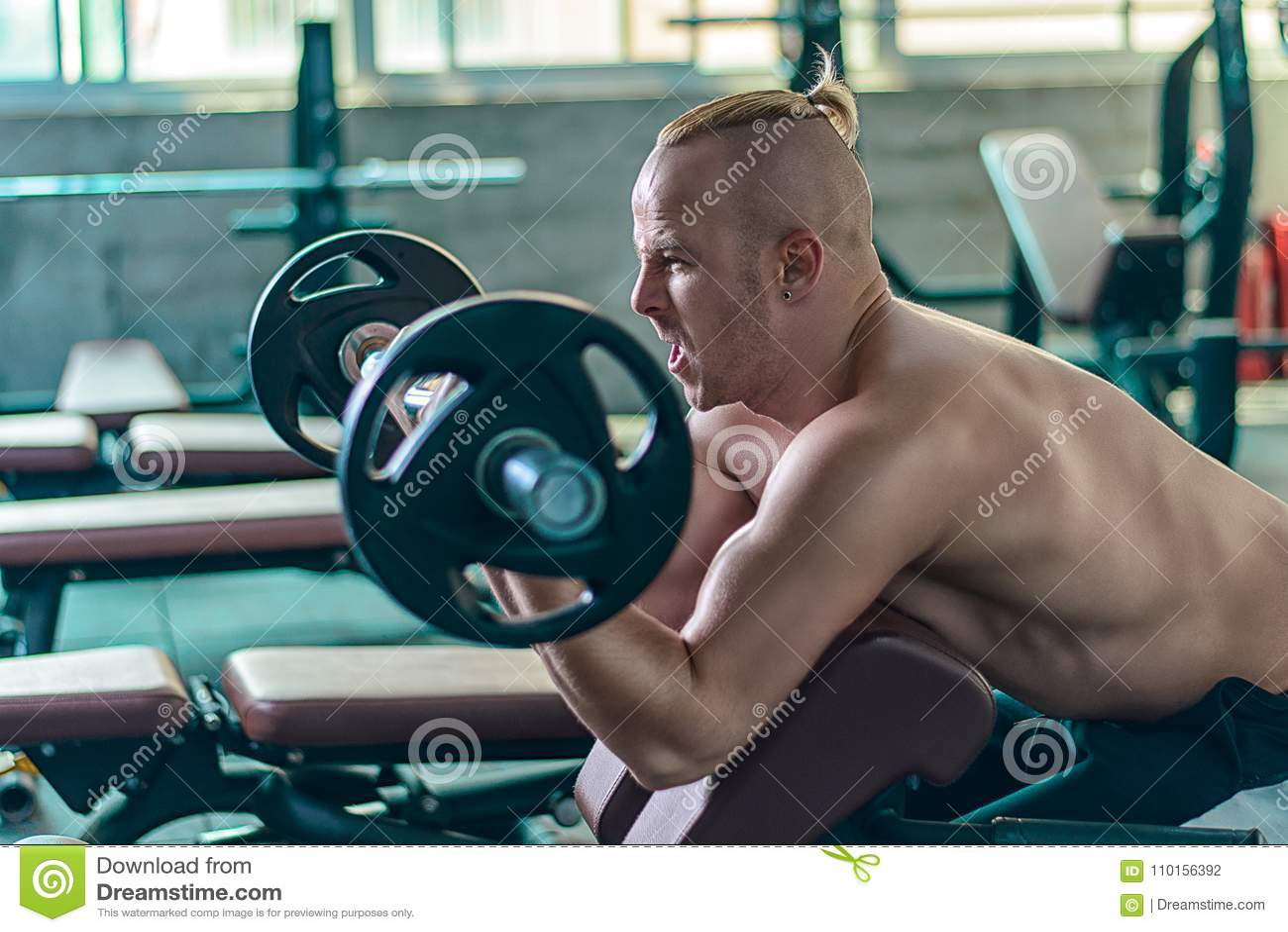 O homem atlético forte faz o exercício com as ondas do pregador