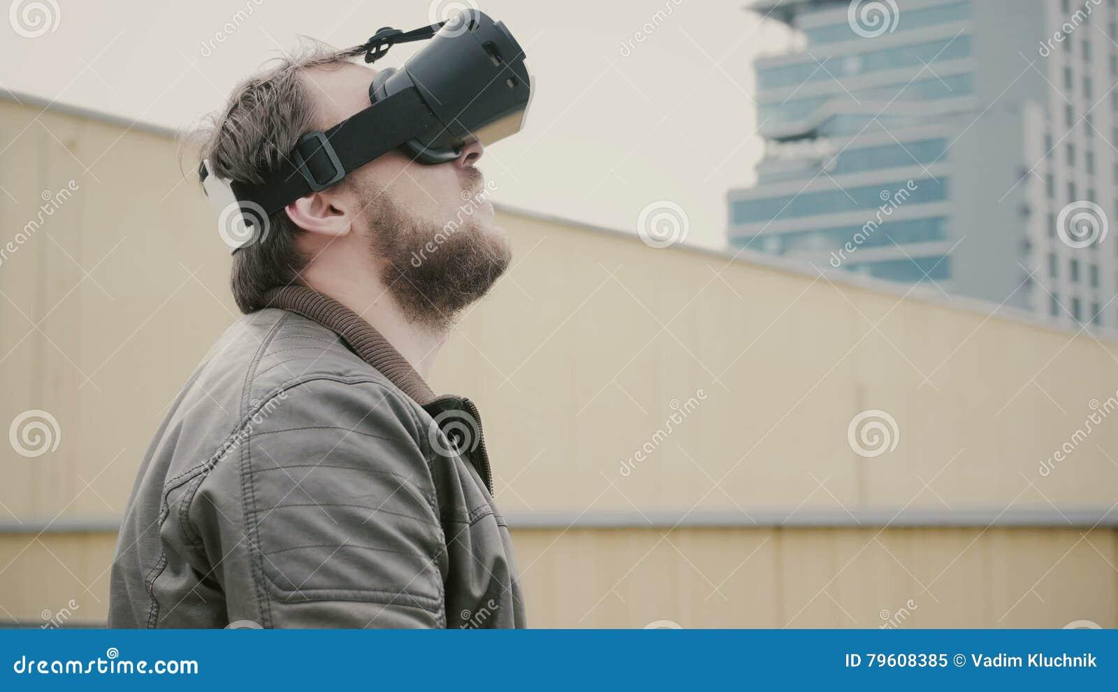 O homem atrativo farpado usa vidros da realidade virtual no telhado 4K