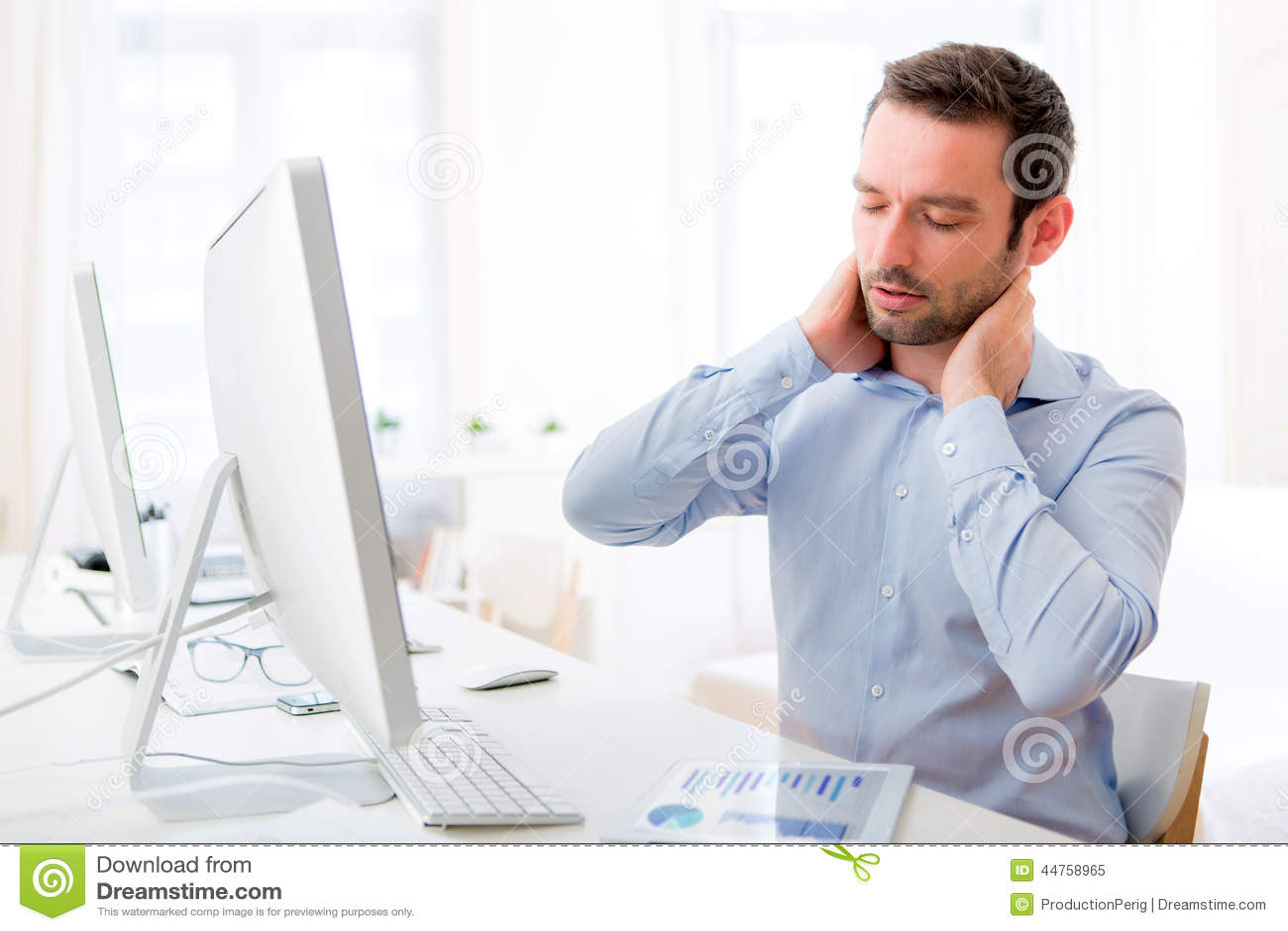 O homem atrativo novo obteve uma dor de pescoço no escritório