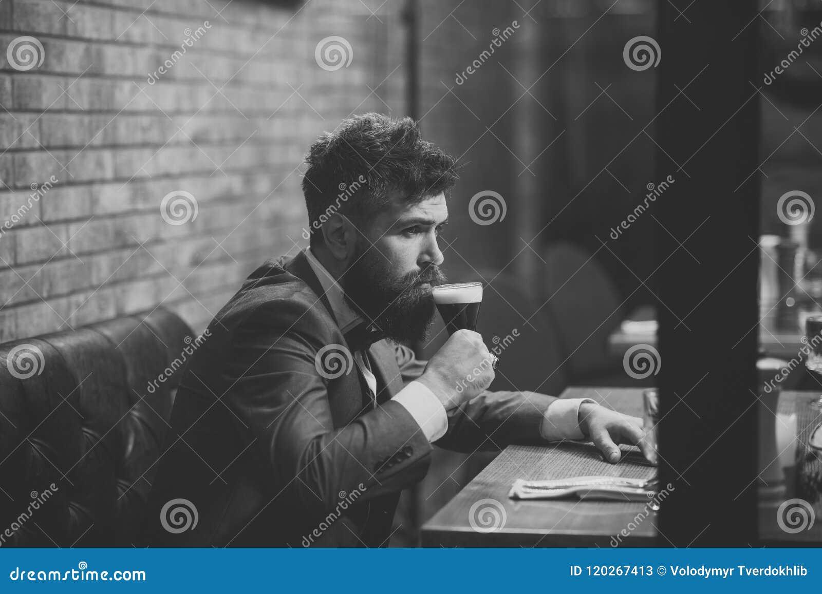 O homem bebe o conhaque Tempo da cerveja Equipe a cerveja bebendo no restaurante na reunião ou na data