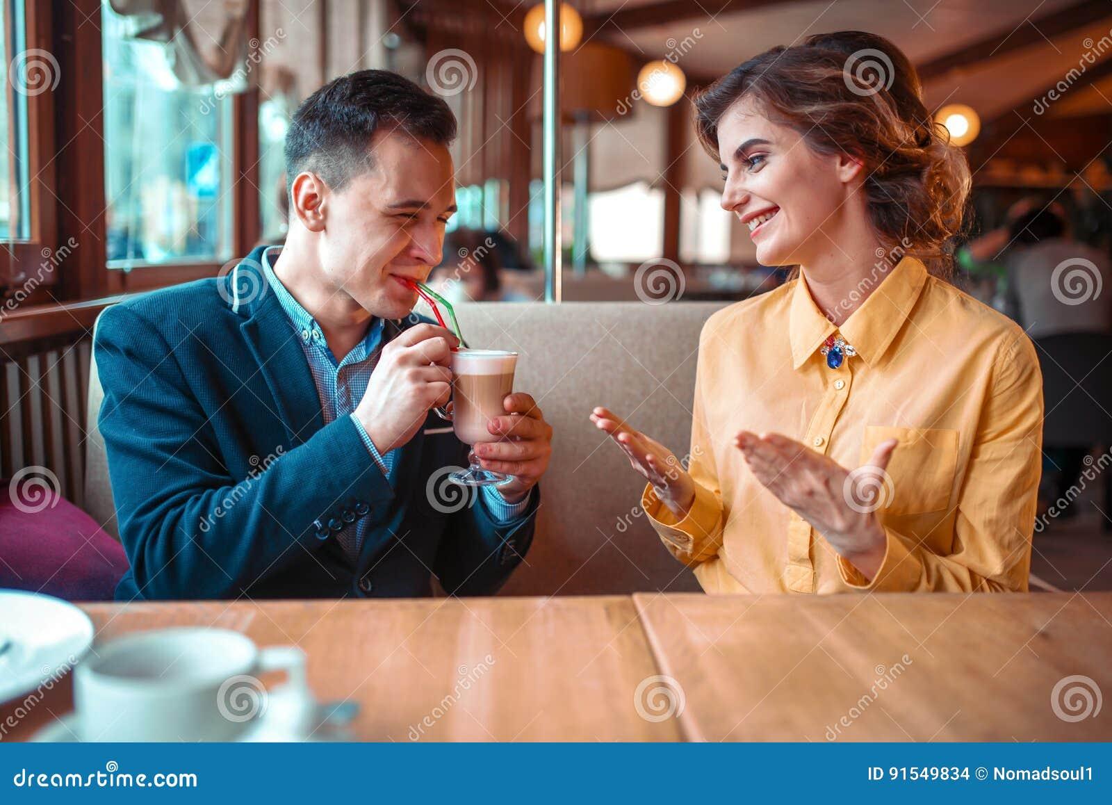 O homem bebe um cocktail da palha contra a mulher