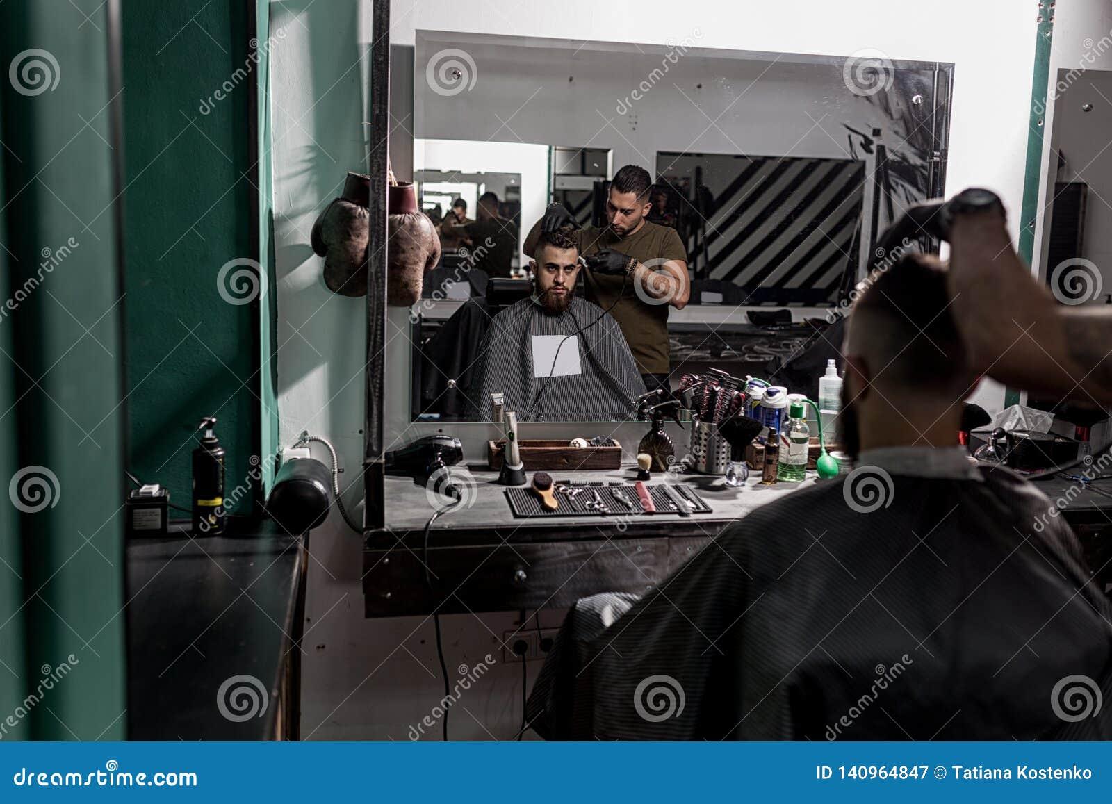 O homem brutal senta na cadeira em uma barbearia na parte dianteira o espelho As barbeações do barbeiro equipam os cabelos no lad