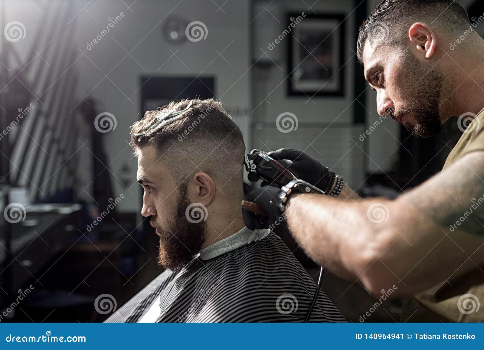 O homem brutal senta-se na cadeira em uma barbearia O barbeiro em luvas pretas barbeia os cabelos do homem na parte traseira