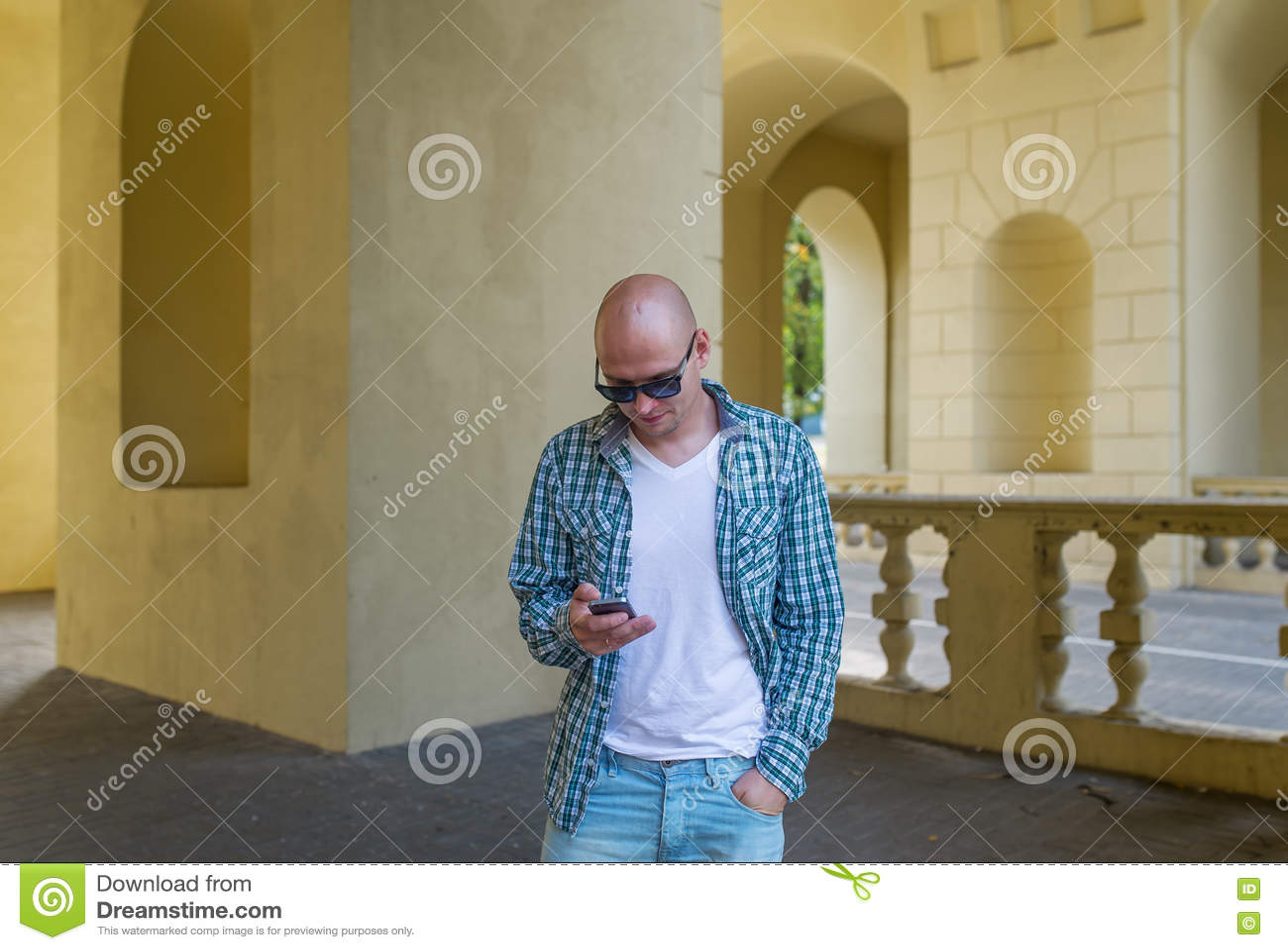 O Homem Calvo Nos óculos De Sol Chama Pelo Telefone Foto de Stock ... 3aa45c0c30