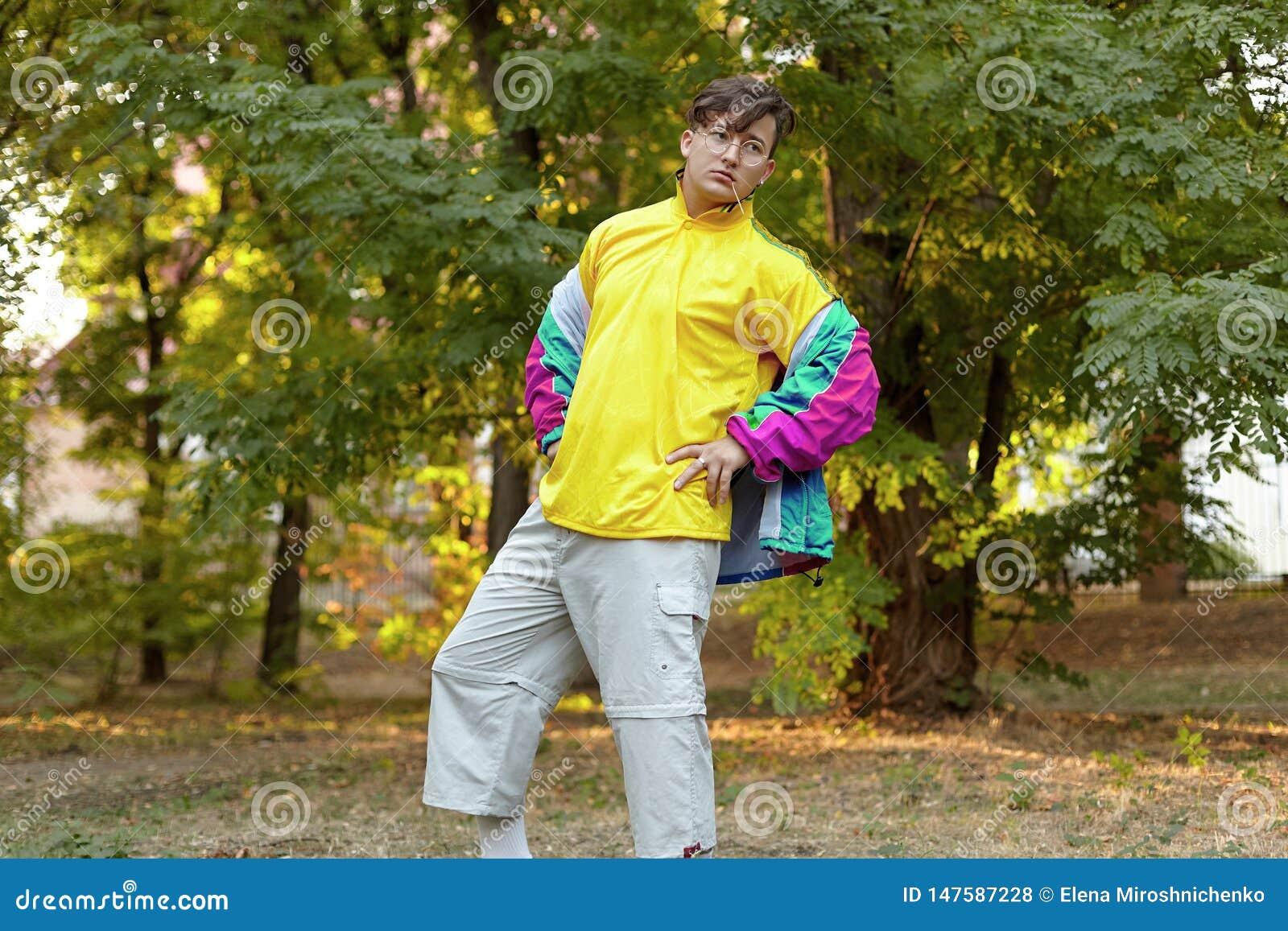 O homem caucasiano considerável novo com estilo freaky brilhante do sportswear 70s está em um parque da manhã Vara na boca, vidro