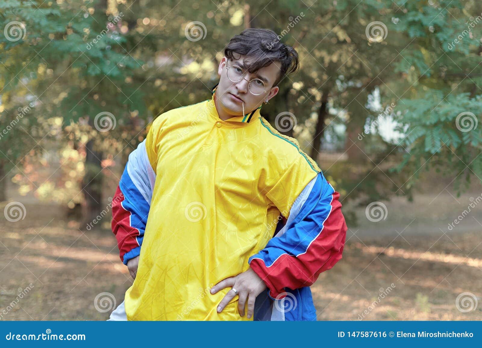 O homem caucasiano consider?vel novo com estilo freaky brilhante do sportswear 70s est? em um parque da manh? Vara na boca, vidro
