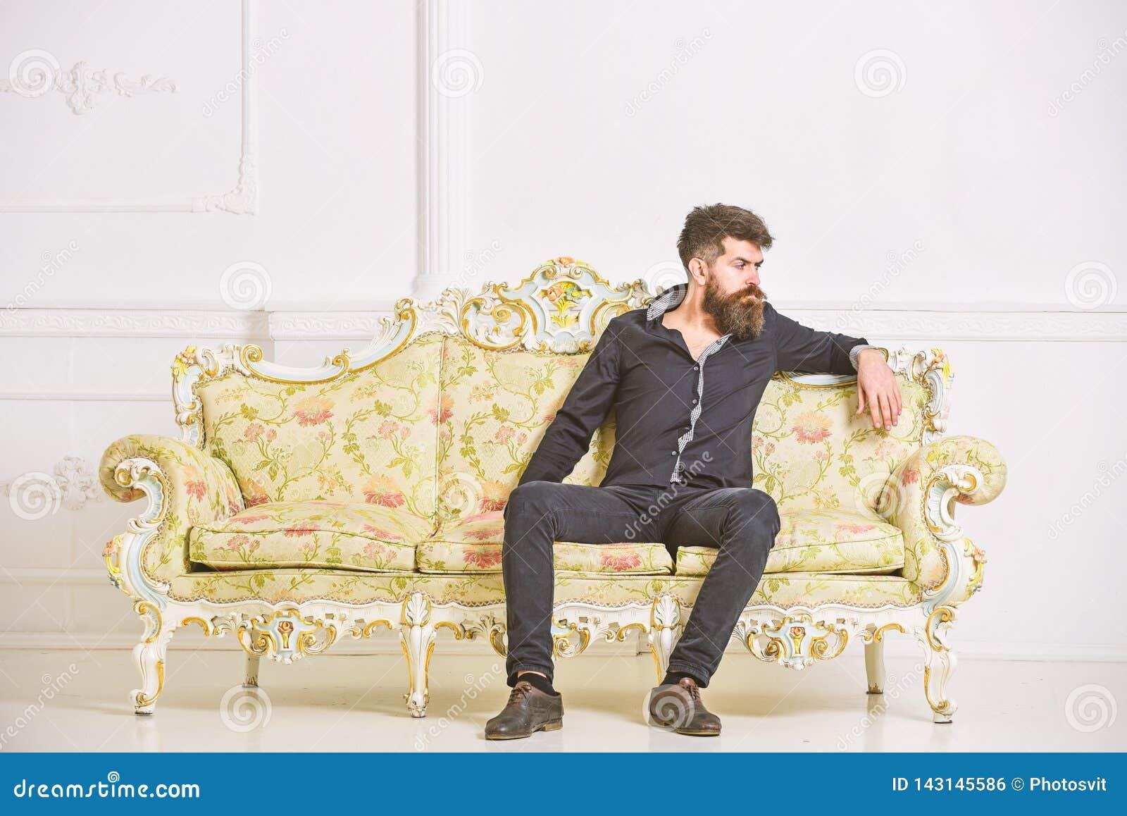 O homem com barba e bigode gasta o lazer na sala de visitas luxuosa O moderno na cara pensativa senta-se apenas Rico e só