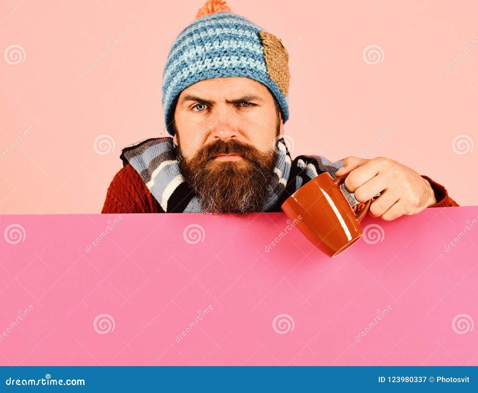 O homem com barba guarda o copo marrom de curar o pó
