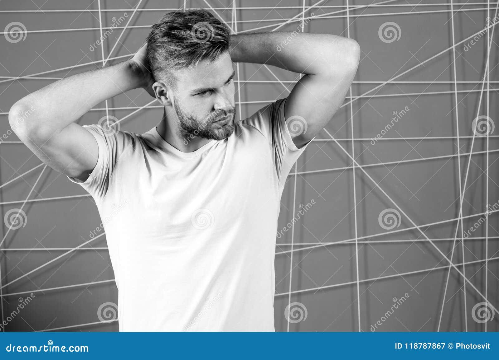 O homem com a cara restrita da cerda aprecia o frescor do cabelo, fundo cor-de-rosa Atrativo farpado do indivíduo com penteado Ho
