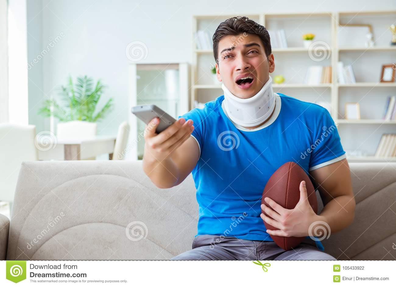 O homem com ferimento do pescoço que olha o futebol americano em casa