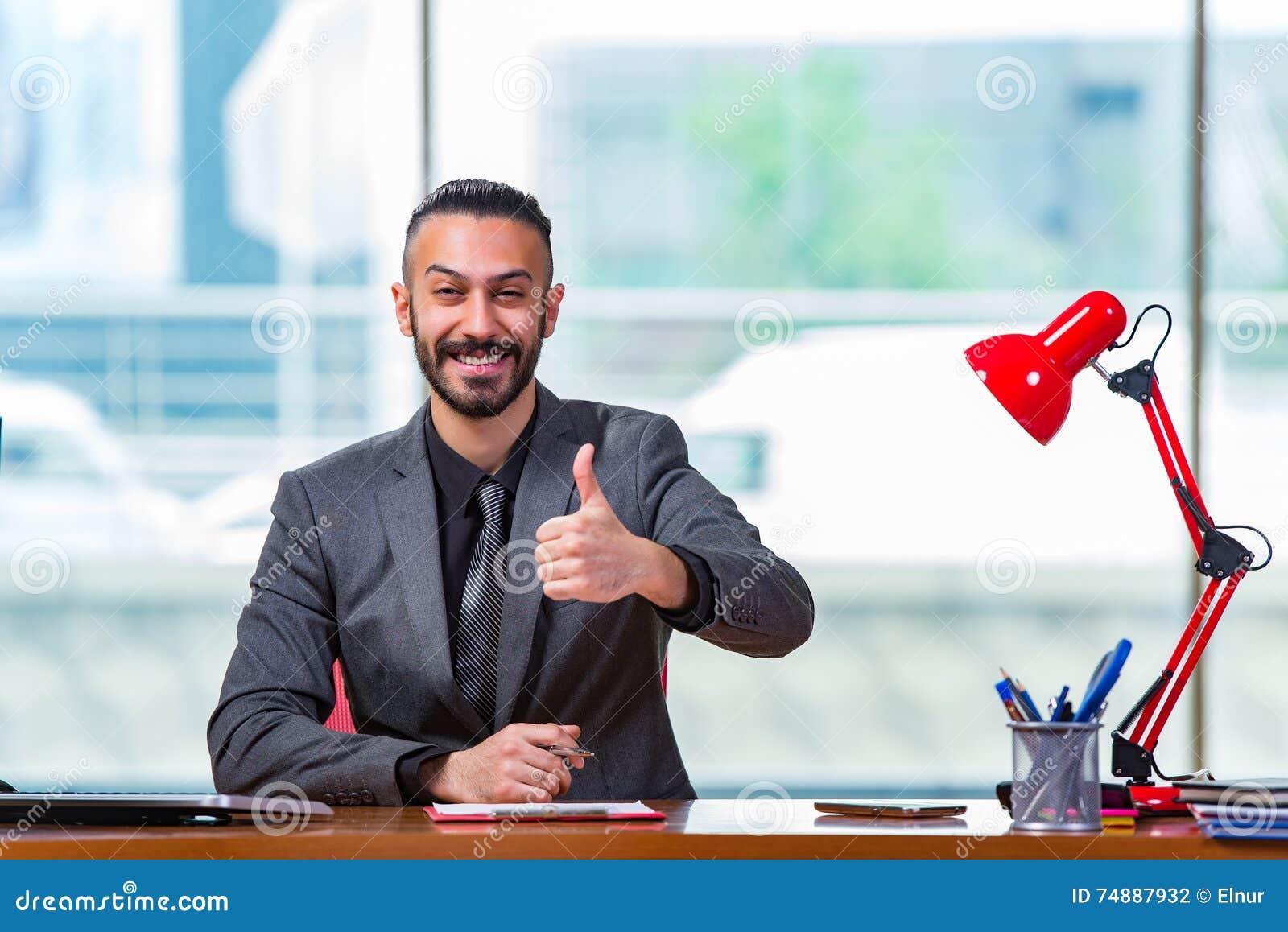 O homem com seus polegares acima na mesa de escritório