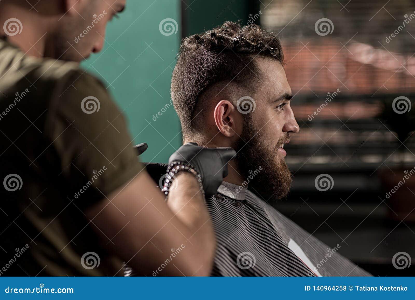 O homem considerável brutal com barba senta-se em uma barbearia O barbeiro barbeia os cabelos no pescoço