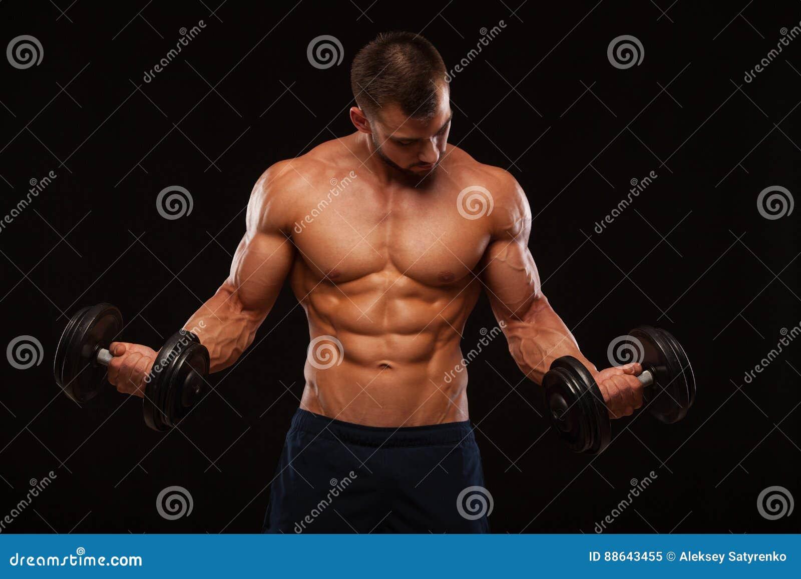 o homem considerável muscular está treinando com pesos no gym