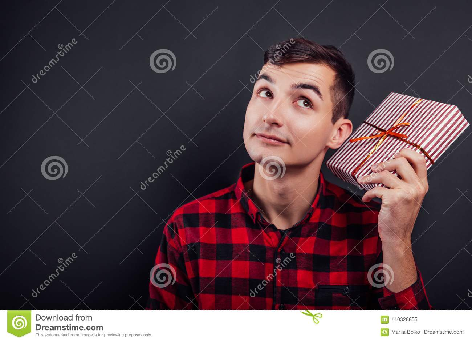 O homem considerável novo agita uma caixa de presente para encontrar que ` s nele