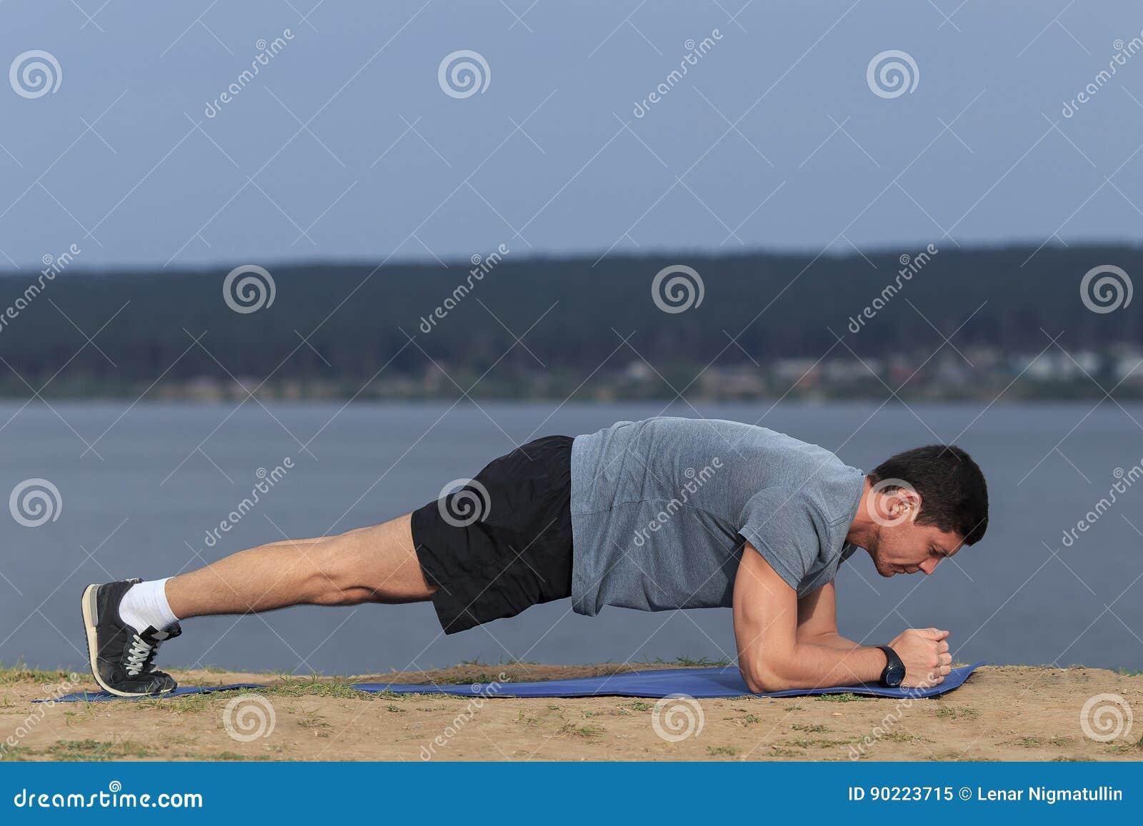 O homem da aptidão do treinamento de Crossfit que faz o exercício do núcleo da prancha que da certo seu núcleo da seção mestra mu