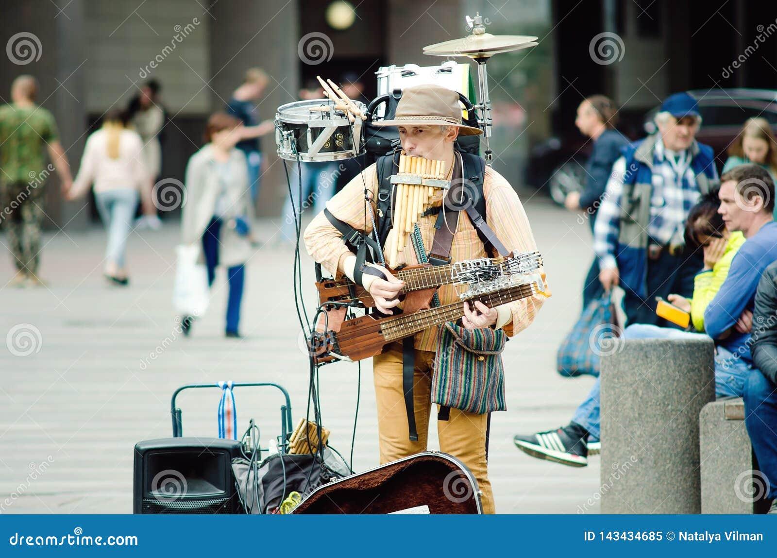 O homem da orquestra joga na rua para transeuntes em St Petersburg