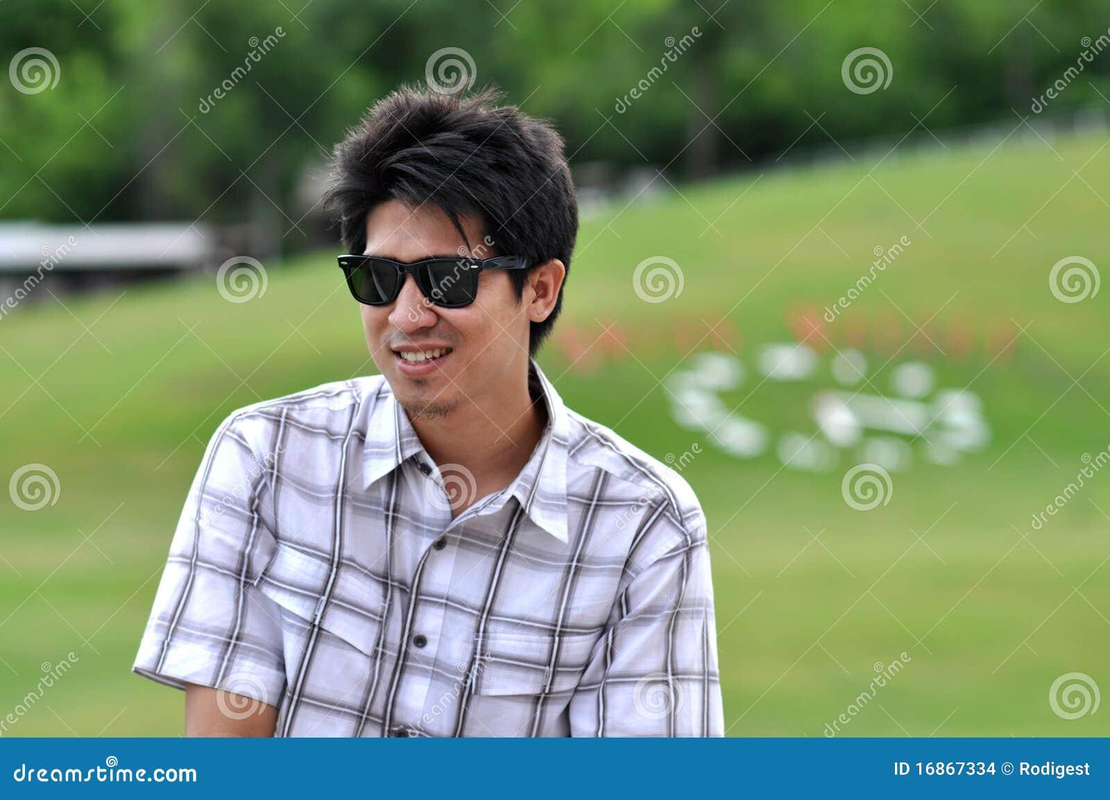 O homem de Ásia Tailândia senta óculos de sol do sorriso