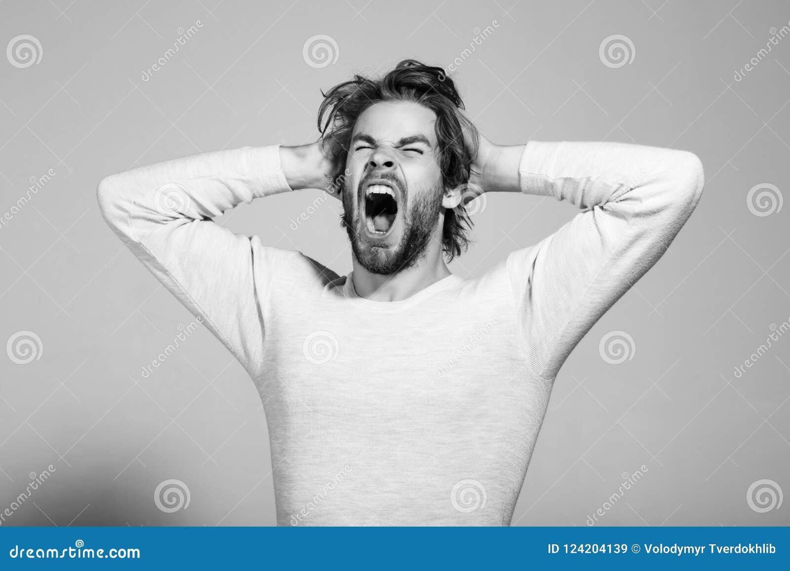 O homem de bocejo sonolento com cabelo uncombed longo, manhã acorda