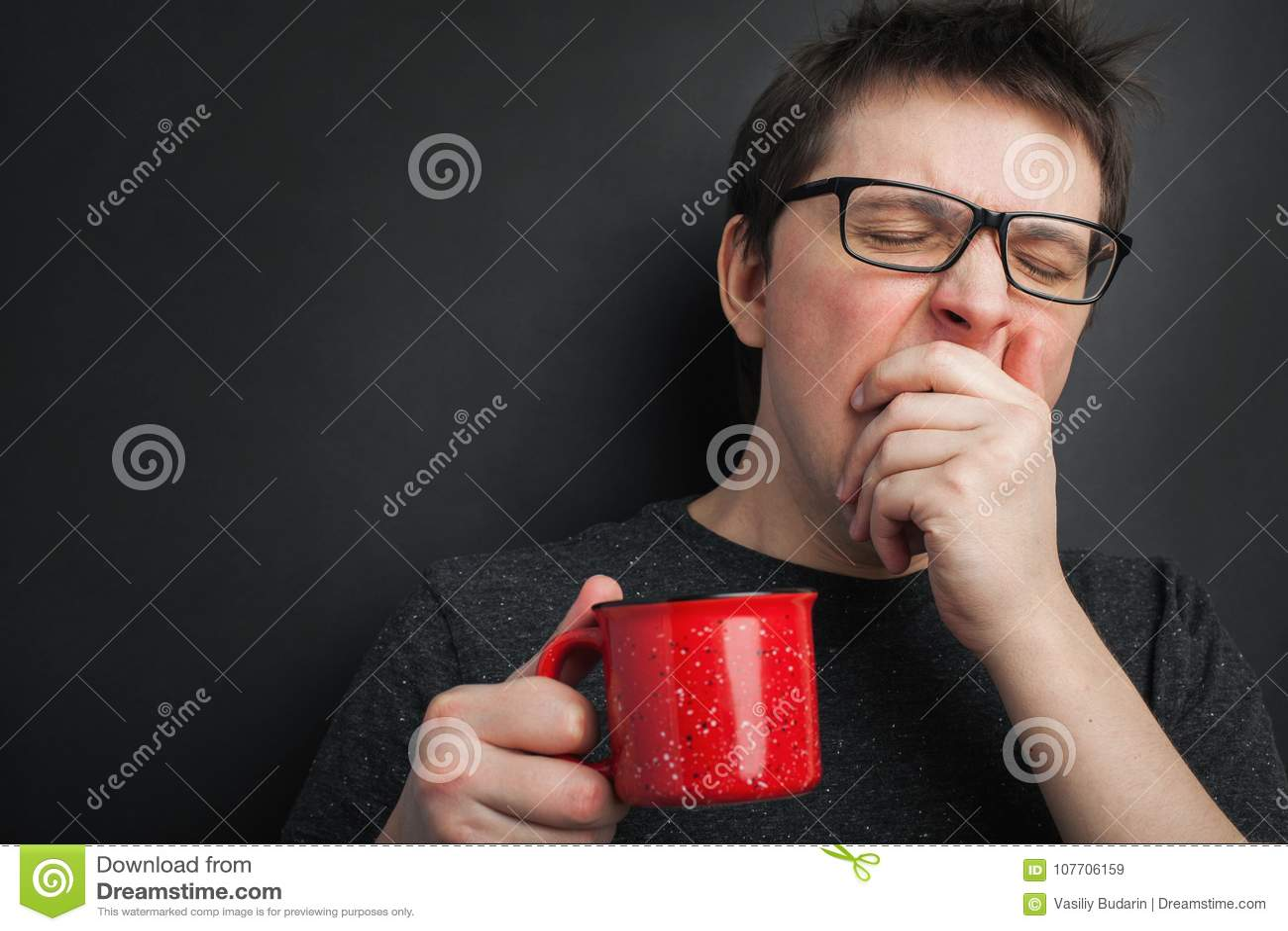 O homem de bocejo sonolento nos monóculos com o copo vermelho do chá ou do café tem cabelo uncombed no roupa interior no fundo pr