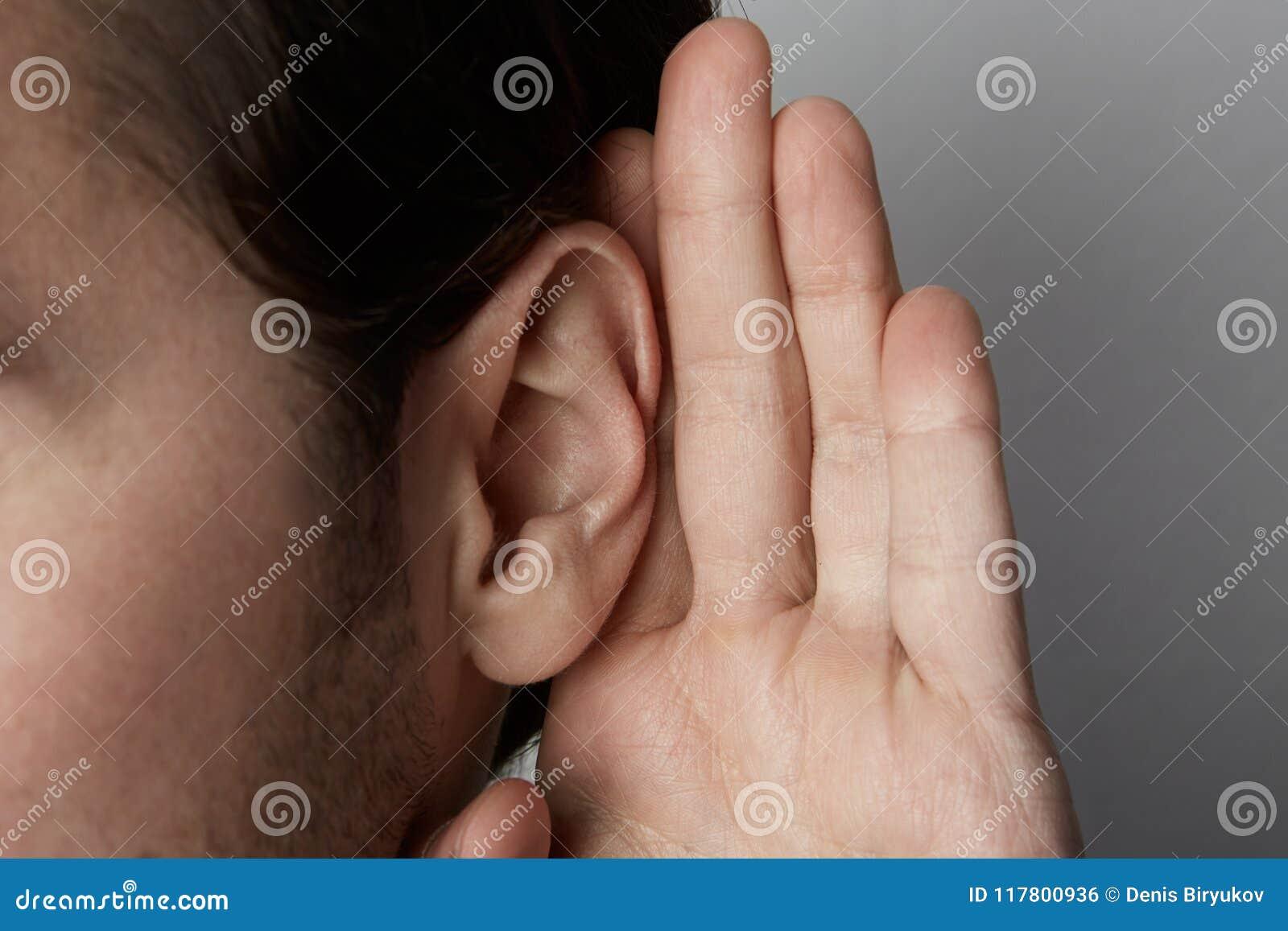 O homem de escuta guarda sua mão perto de sua orelha sobre o fundo cinzento closeup