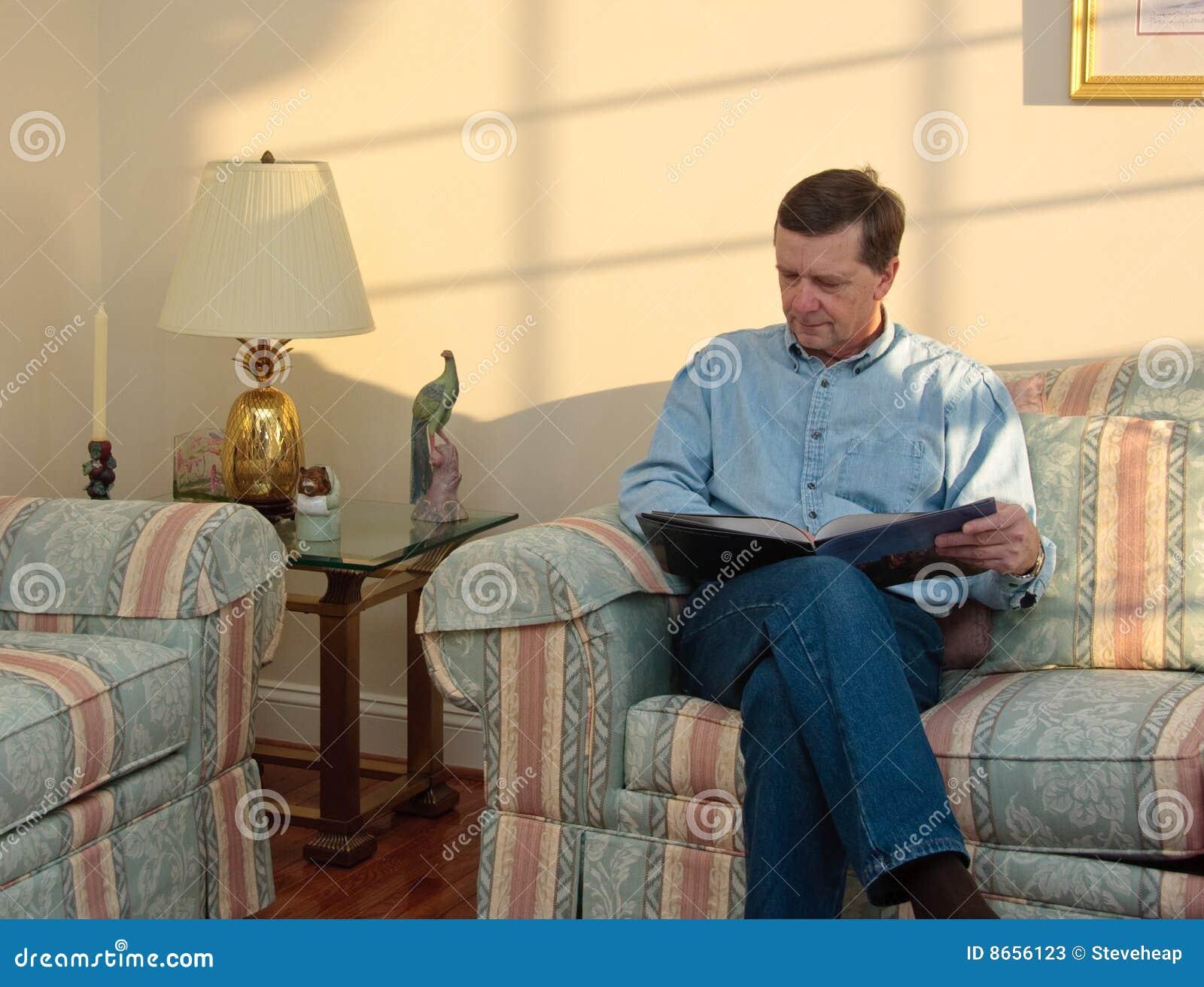O homem de meia idade relaxa no sofá
