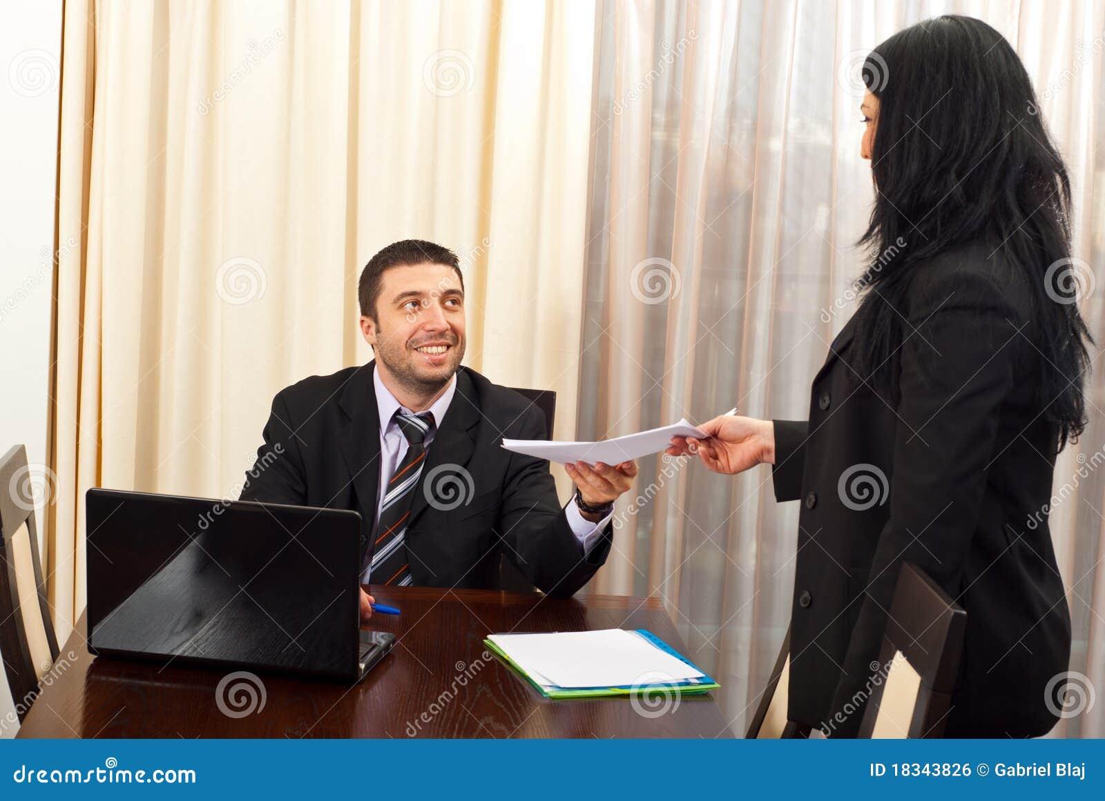O homem de negócio feliz dá papéis à secretária