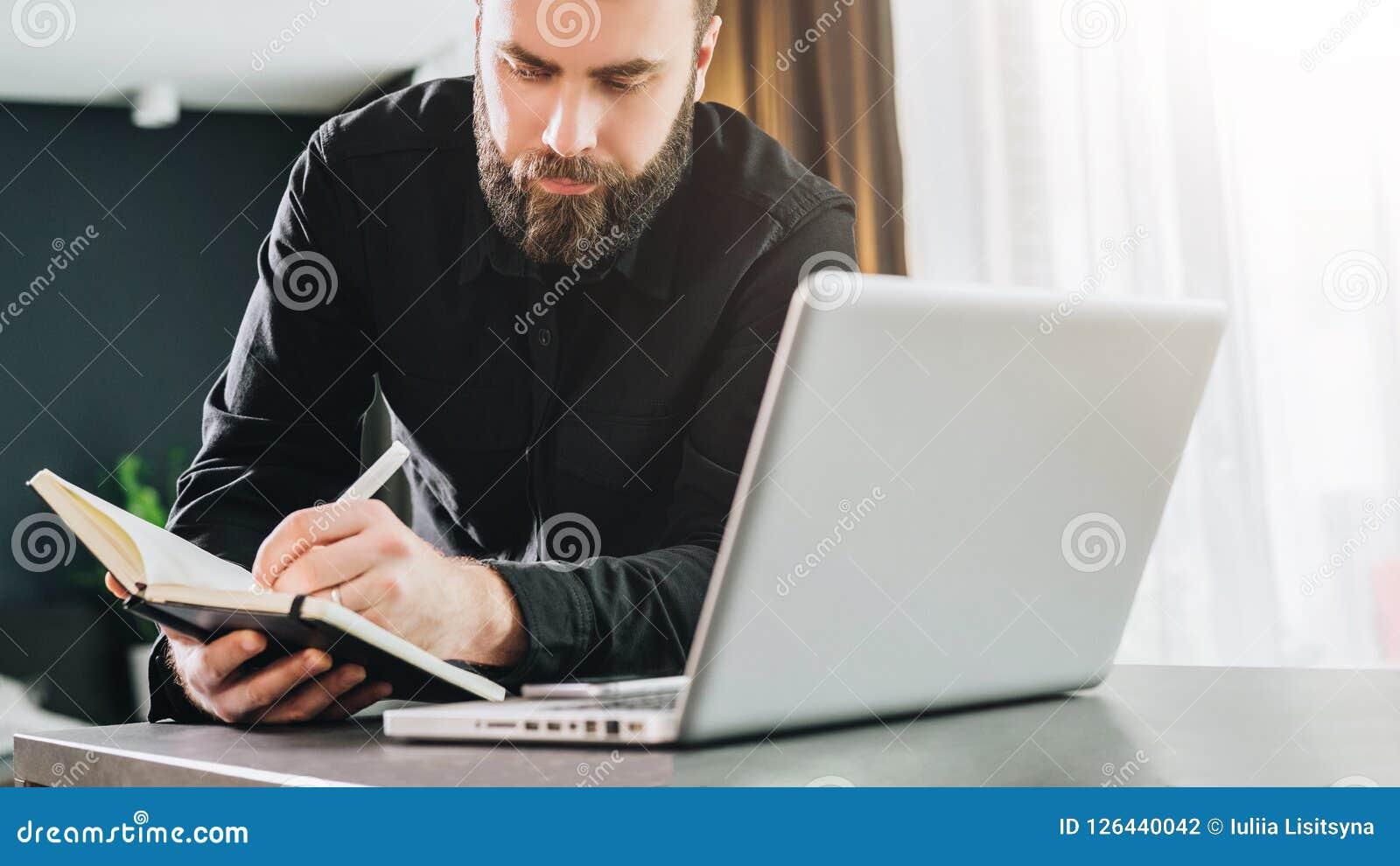 O homem de negócios é o computador próximo ereto, funcionamento no portátil, fazendo anotações no caderno Observação do homem web