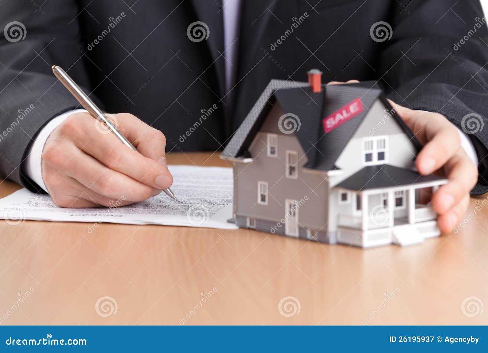 O homem de negócios assina o contrato atrás do architectu da casa