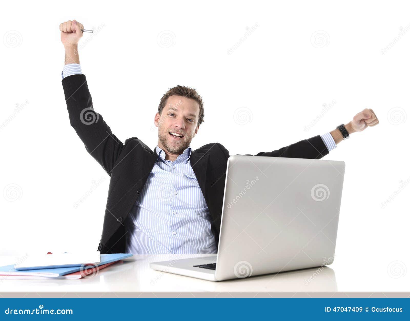 O homem de negócios atrativo novo feliz e hético no trabalho de escritório que senta-se na mesa do computador satisfez a comemora